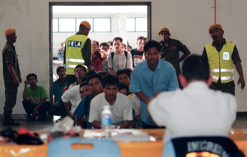 Indonesian illegal immigrants wait for Malaysian immigration checks at Port Klang, outside Kuala Lumpur, February 28, 2005. REUTERS/Kamarulzaman Russali/File Photo