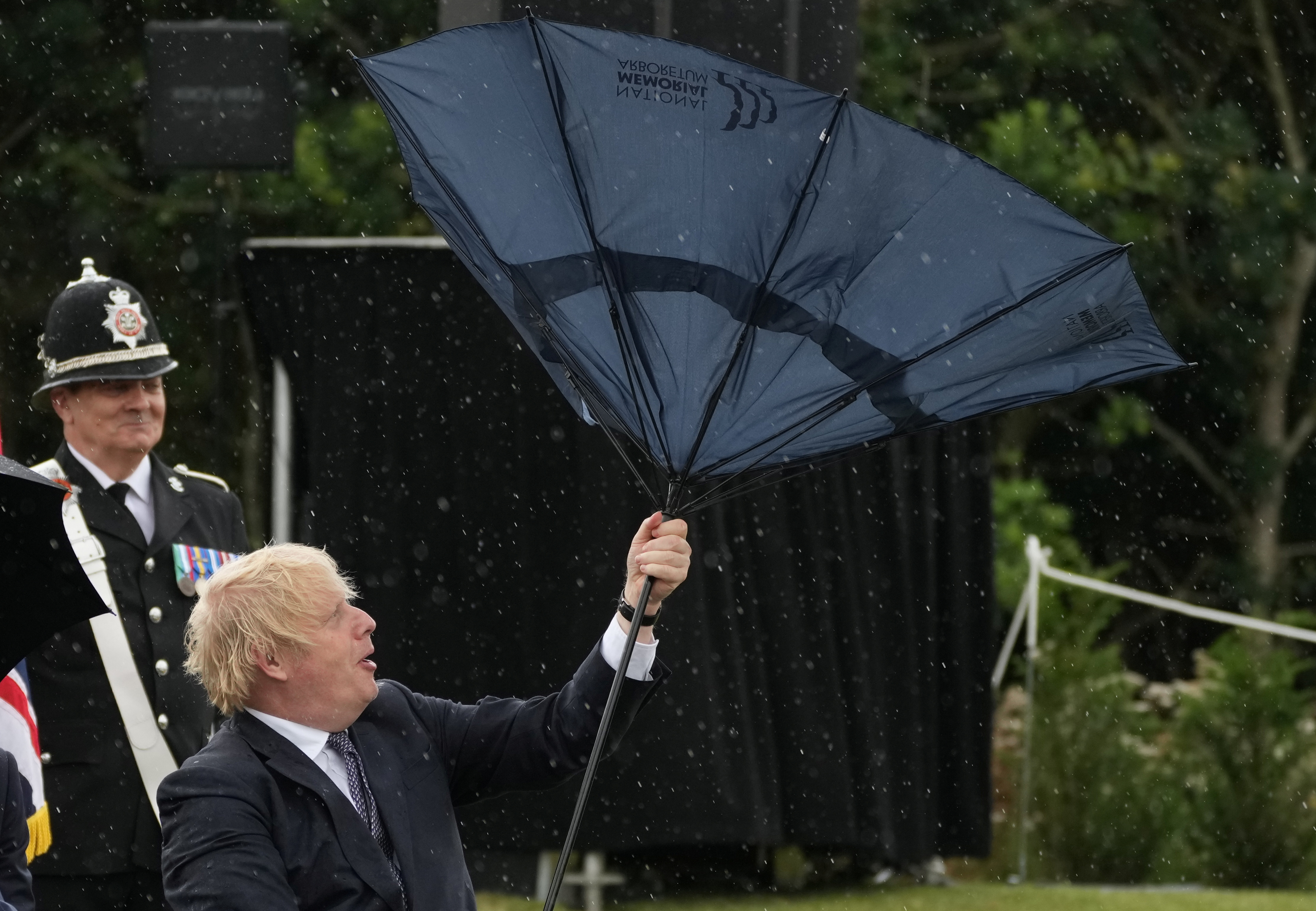 Britain's Prime Minister Boris Johnson struggles with an umbrella during a visit to the National Memorial Arboretum at Alrewas, Staffordshire, Britain July 28, 2021. Christopher Furlong/Pool via REUTERS