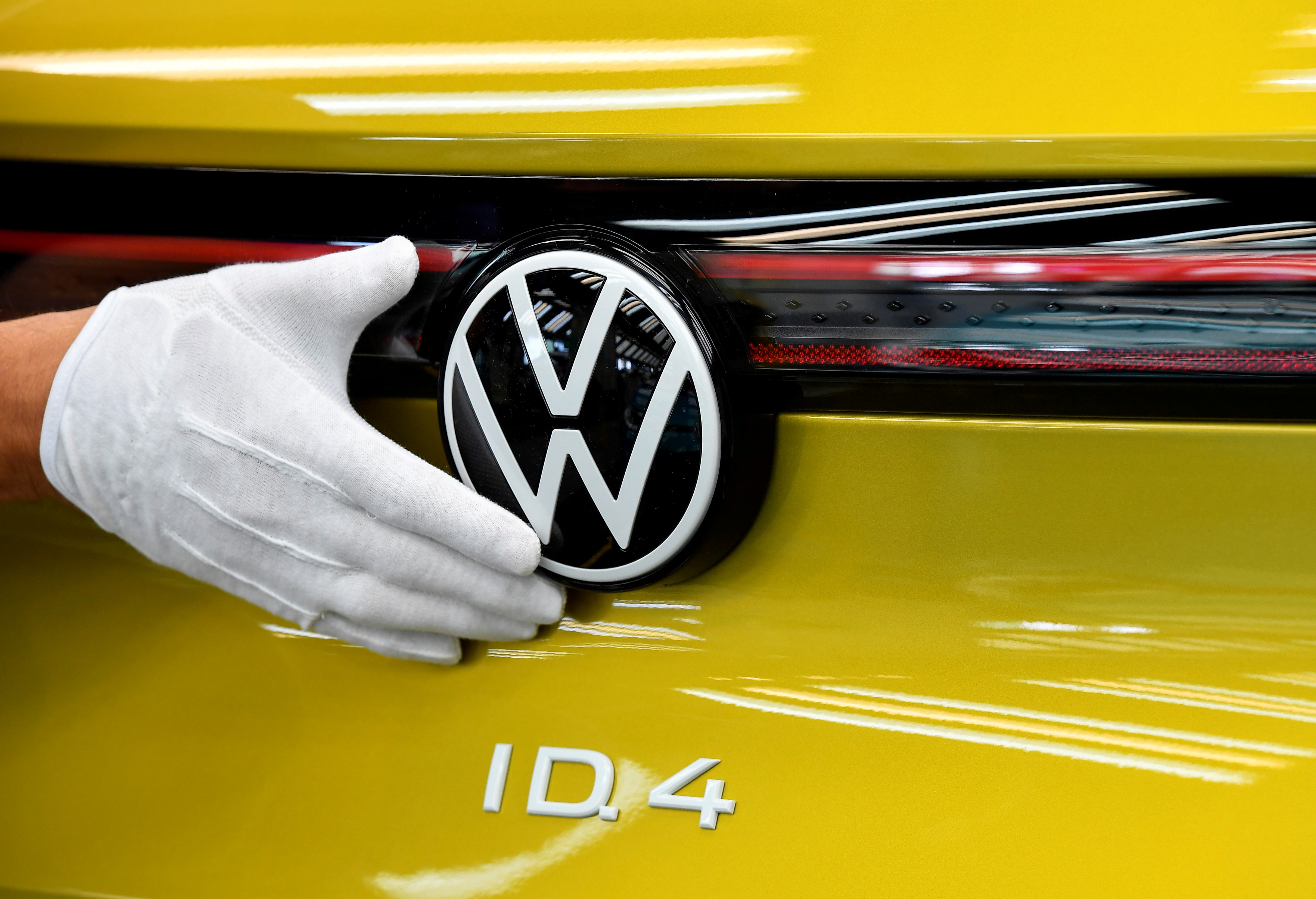 A technical employee cleans the paint in the final inspection at the production line for the electric Volkswagen model ID.4, in Zwickau, Germany, September 18, 2020. REUTERS/Matthias Rietschel