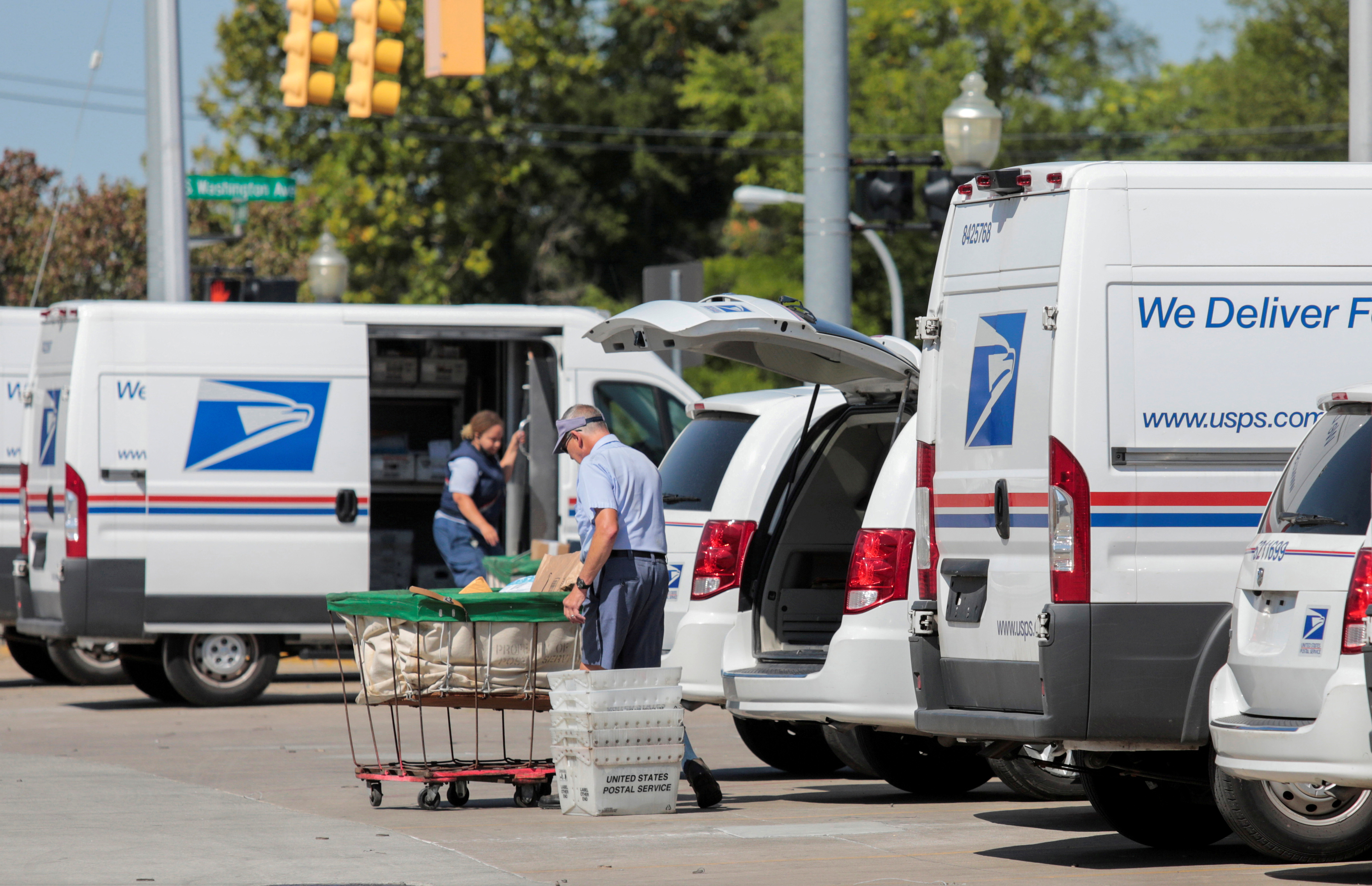 United States Postal Service (USPS) workers load mail into delivery trucks outside a post office in Royal Oak, Michigan, U.S. August 22, 2020. REUTERS/Rebecca Cook