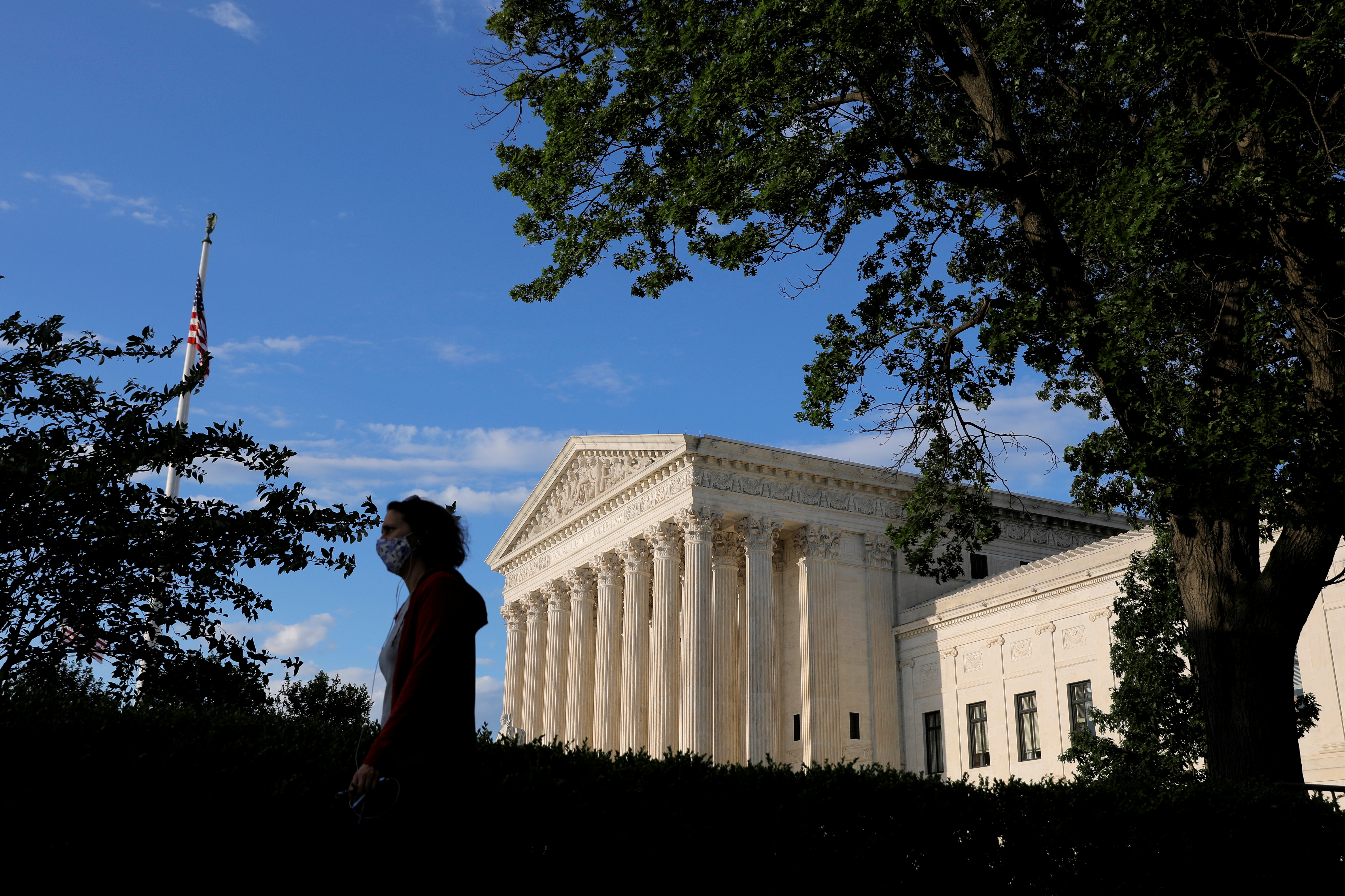 A person in a mask walks past the United States Supreme Court Building in Washington, D.C., U.S., May 13, 2021. REUTERS/Andrew Kelly/File Photo