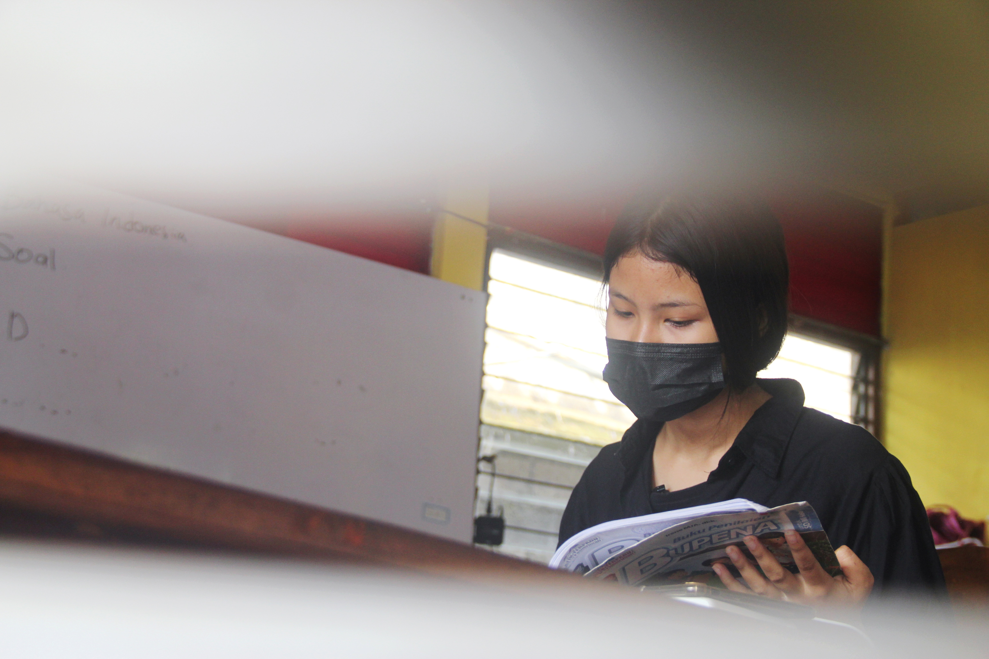 Ni Kadek Suriani, 13, wearing a protective face mask, reads a book as she studies at a Bali Street Mums and Kids shelter after dropping out from school during the coronavirus disease (COVID-19) pandemic, in Denpasar, Bali, Indonesia, September 10, 2021. Picture taken September 10, 2021. REUTERS/Wayan Sukarda