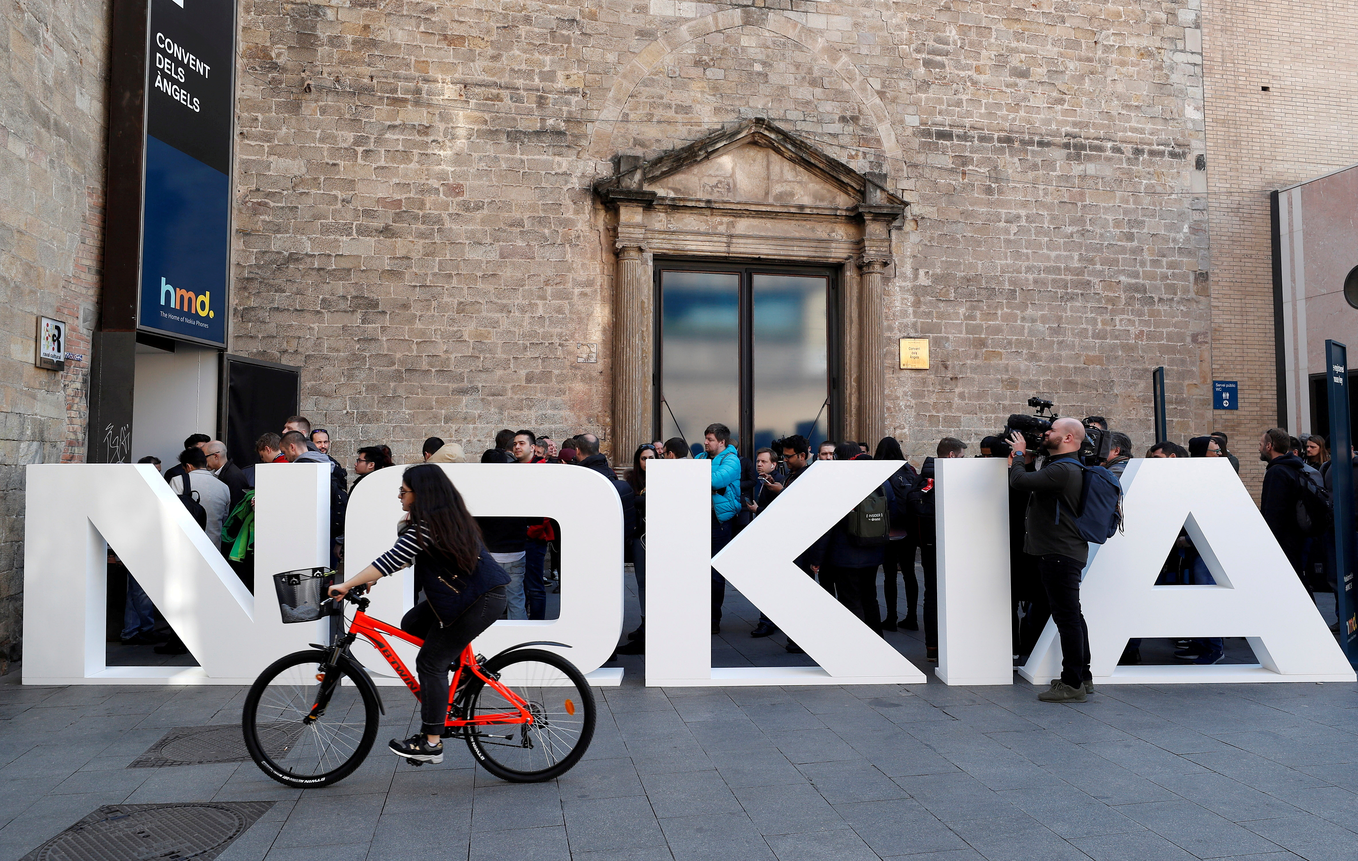 A cyclist rides past a Nokia logo during the Mobile World Congress in Barcelona, Spain February 25, 2018. REUTERS/Yves Herman
