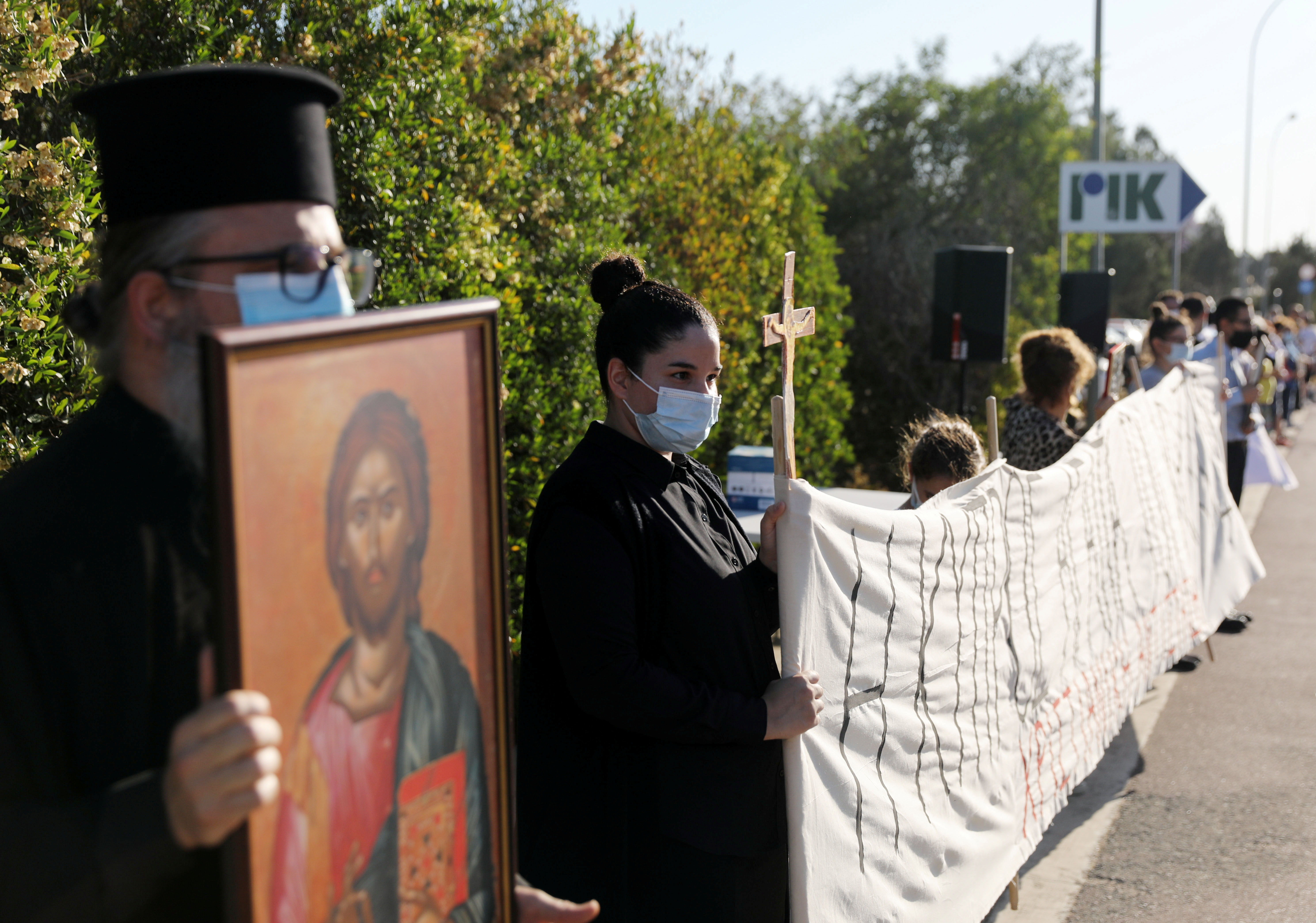 """People hold icons and bunner during a protest against the song """"El Diablo"""", Cyprus pick to represent the island  at the annual Eurovision Song Contest outside the offices of the Cyprus Broadcasting Corporation in Nicosia, Cyprus May 19, 2021. REUTERS/Yiannis Kourtoglou"""