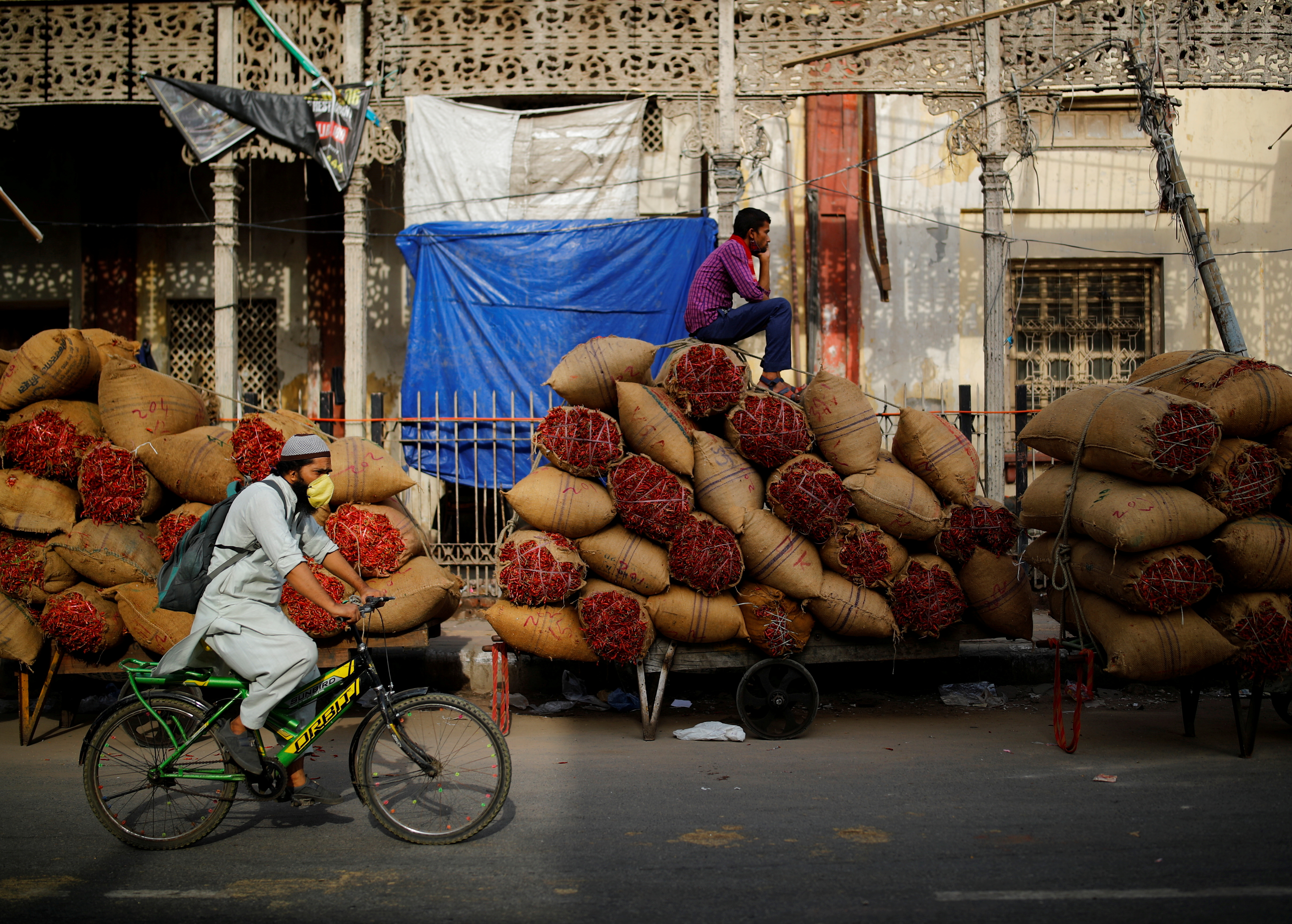 A worker sits on sacks of spices loaded on a cart at a wholesale market after authorities eased lockdown restrictions that were imposed to slow the spread of the coronavirus disease (COVID-19), in the old quarters of Delhi, India, June 8, 2021. REUTERS/Adnan Abidi     TPX IMAGES OF THE DAY