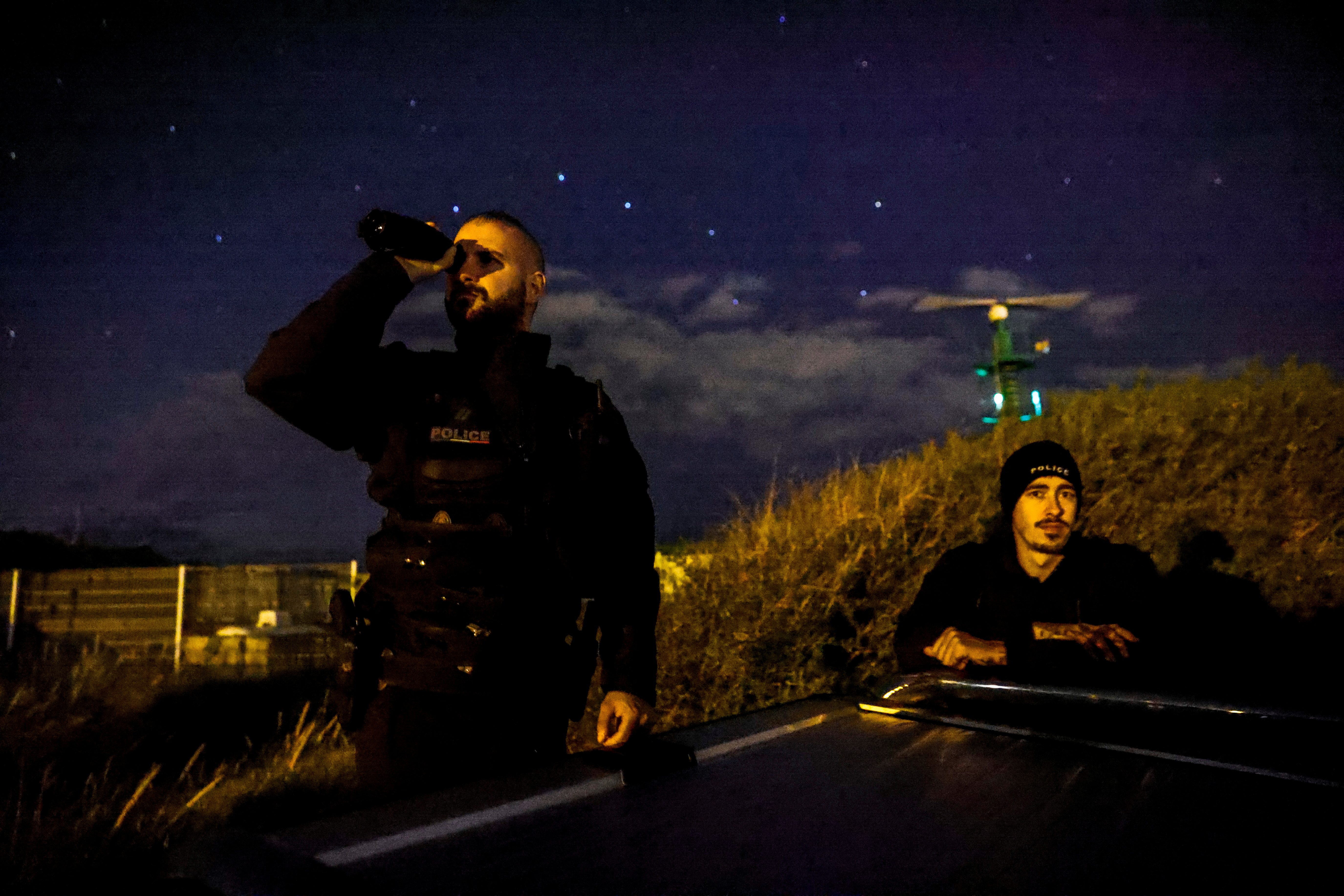 A police officer uses a light intensification monocular as he patrols along the French coast in Sangatte, France, August 4, 2021. REUTERS/Pascal Rossignol
