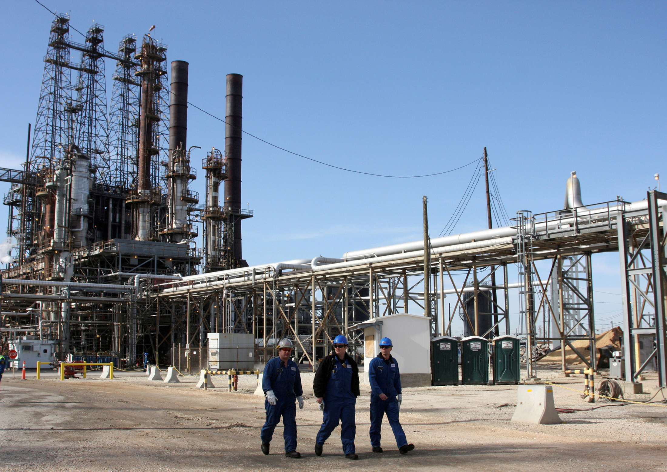 Refinery workers walk inside the LyondellBasell oil refinery in Houston, Texas March 6, 2013. REUTERS/Donna Carson/File Photo