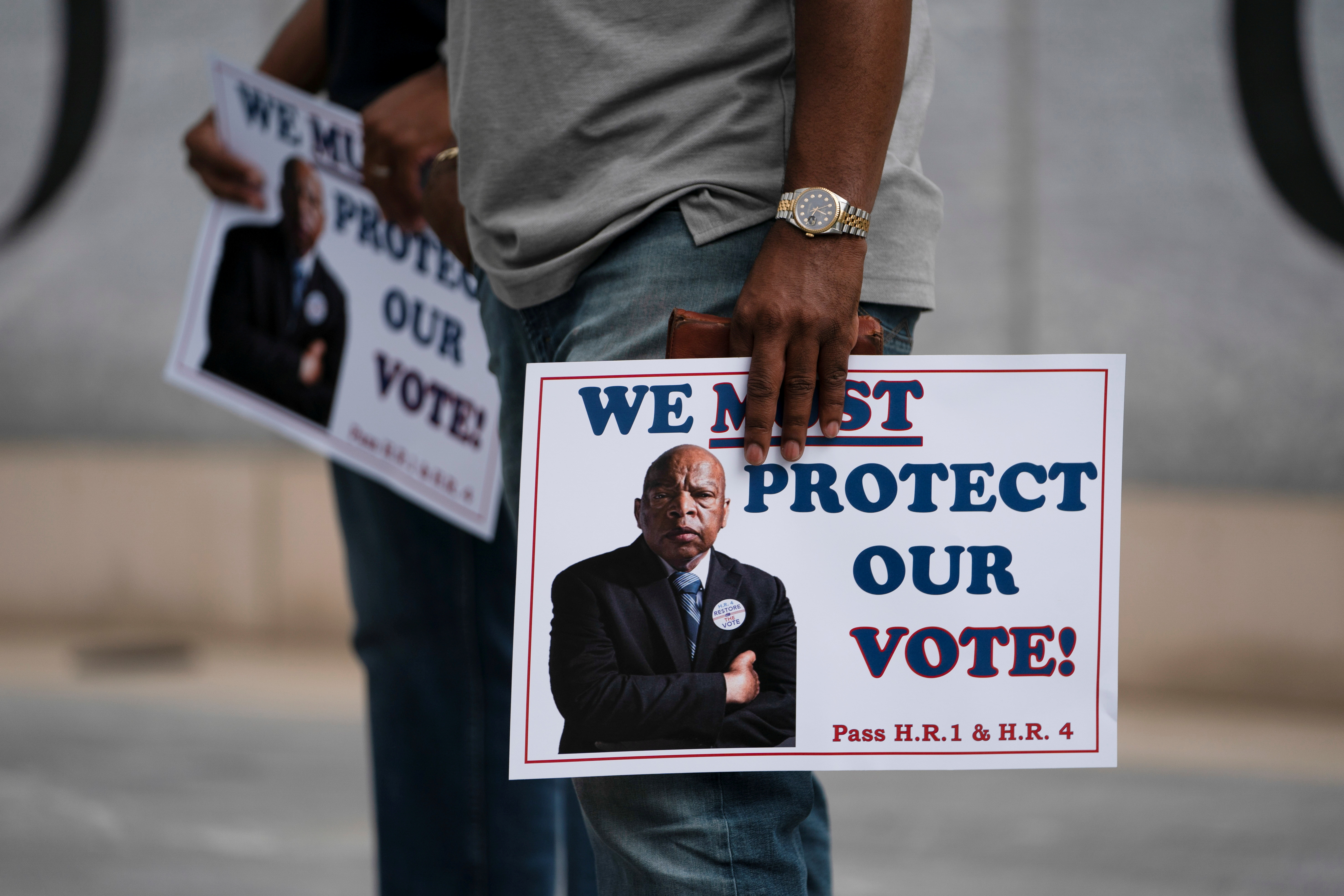 A person holds signs during a rally against the state's new voting restrictions outside the Georgia State Capitol, in Atlanta, Georgia, U.S., June 8, 2021. REUTERS/Elijah Nouvelage/File Photo