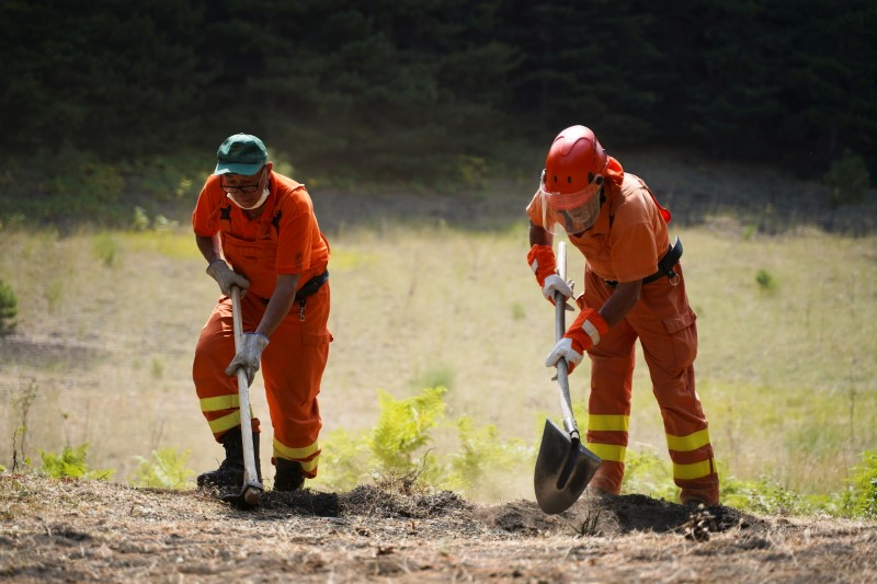 Forest Guard workers dig the ground as they make preparations for possible wildfires as temperatures are expected to continue to peak at over 40 degrees Celsius during a heatwave across southern Italy, in Monte Vetore on Mount Etna, Italy, August 11, 2021. REUTERS/Antonio Parrinello