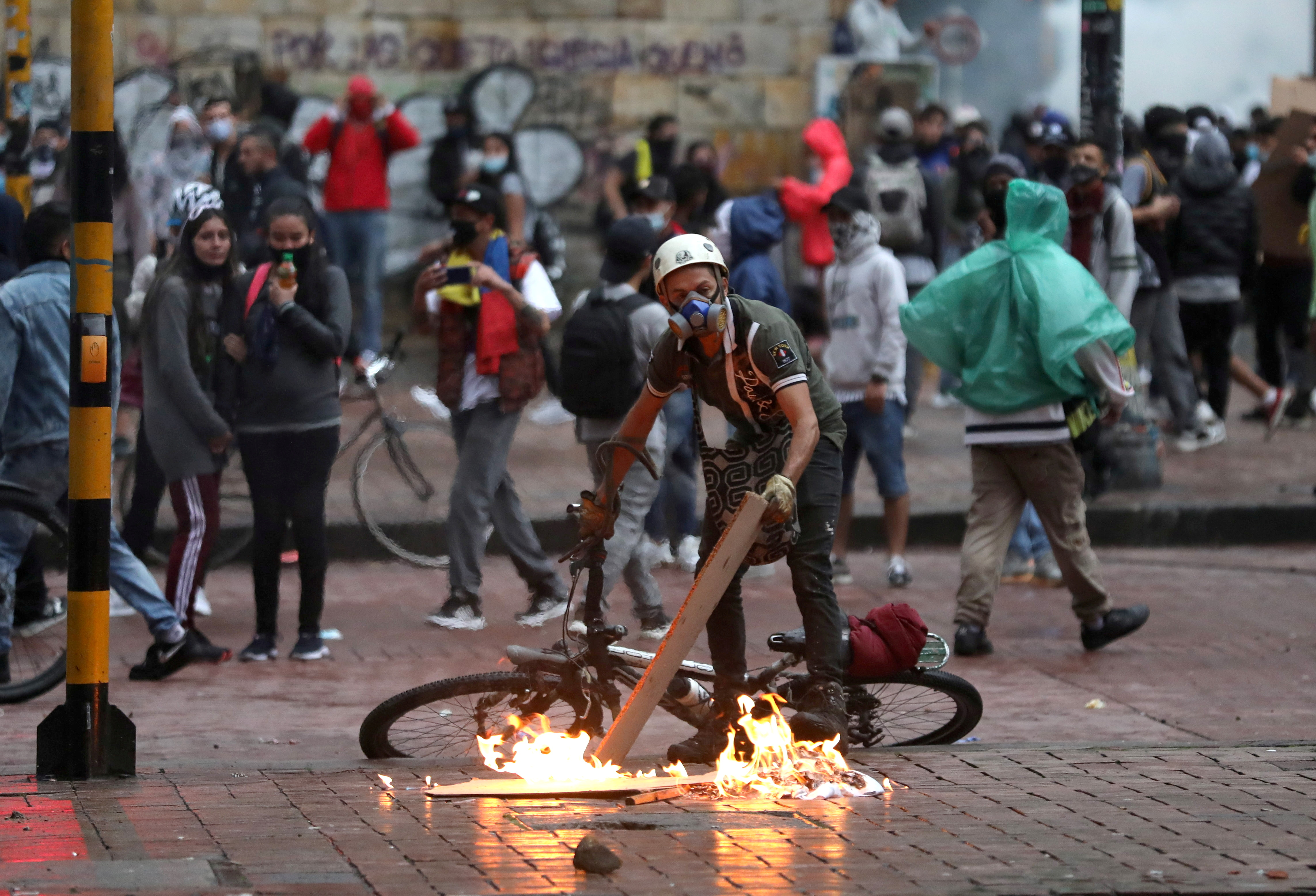 A protester stokes a fire during a protest against the tax reform of President Ivan Duque's government in Bogota, Colombia, May 1, 2021. REUTERS/Luisa Gonzalez/