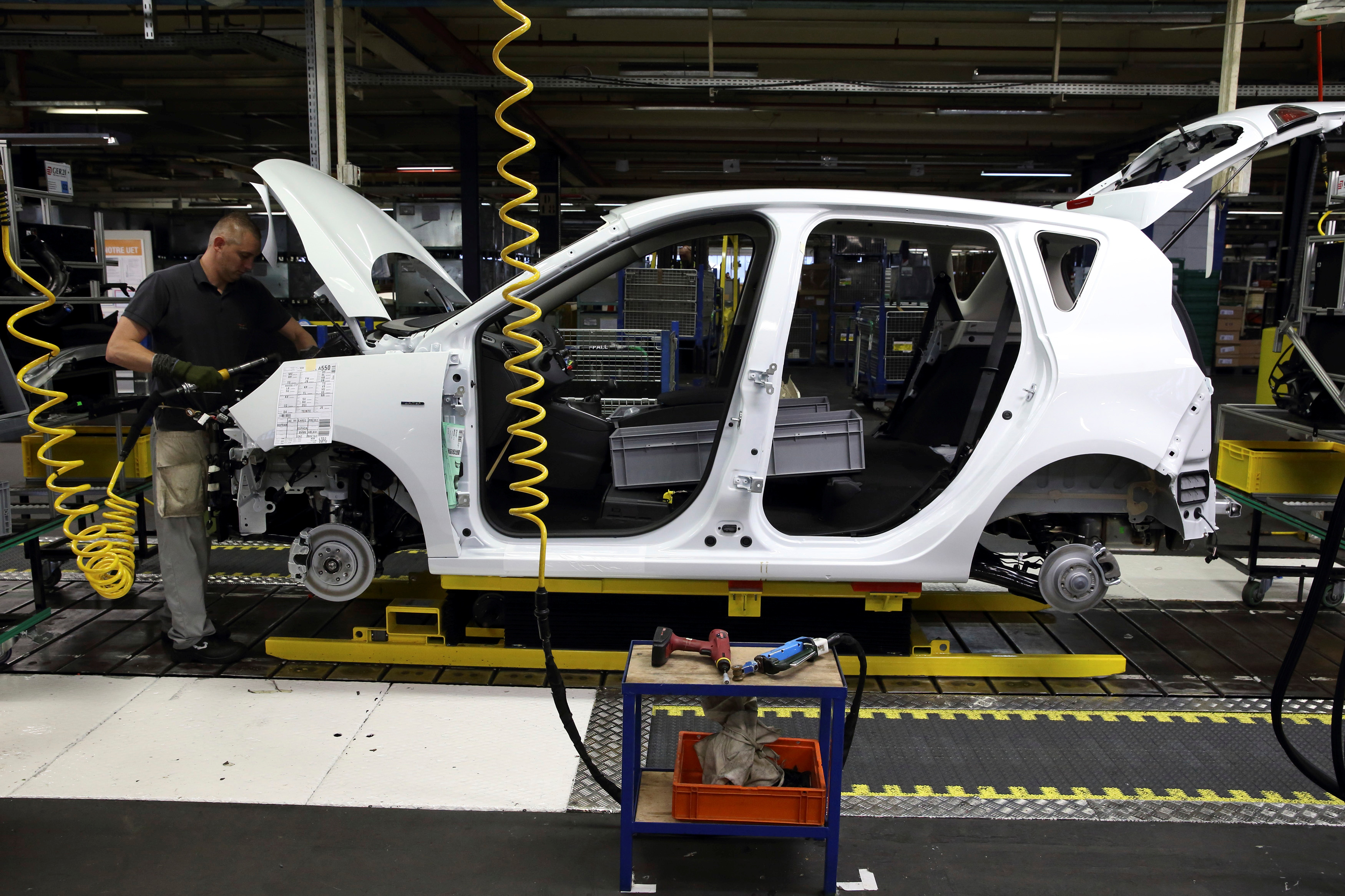 An employee works on a Renault Scenic as it moves along the assembly line at the Renault automobile assembly plant in Douai, northern France, November 26, 2014. REUTERS/Pascal Rossignol/File Photo