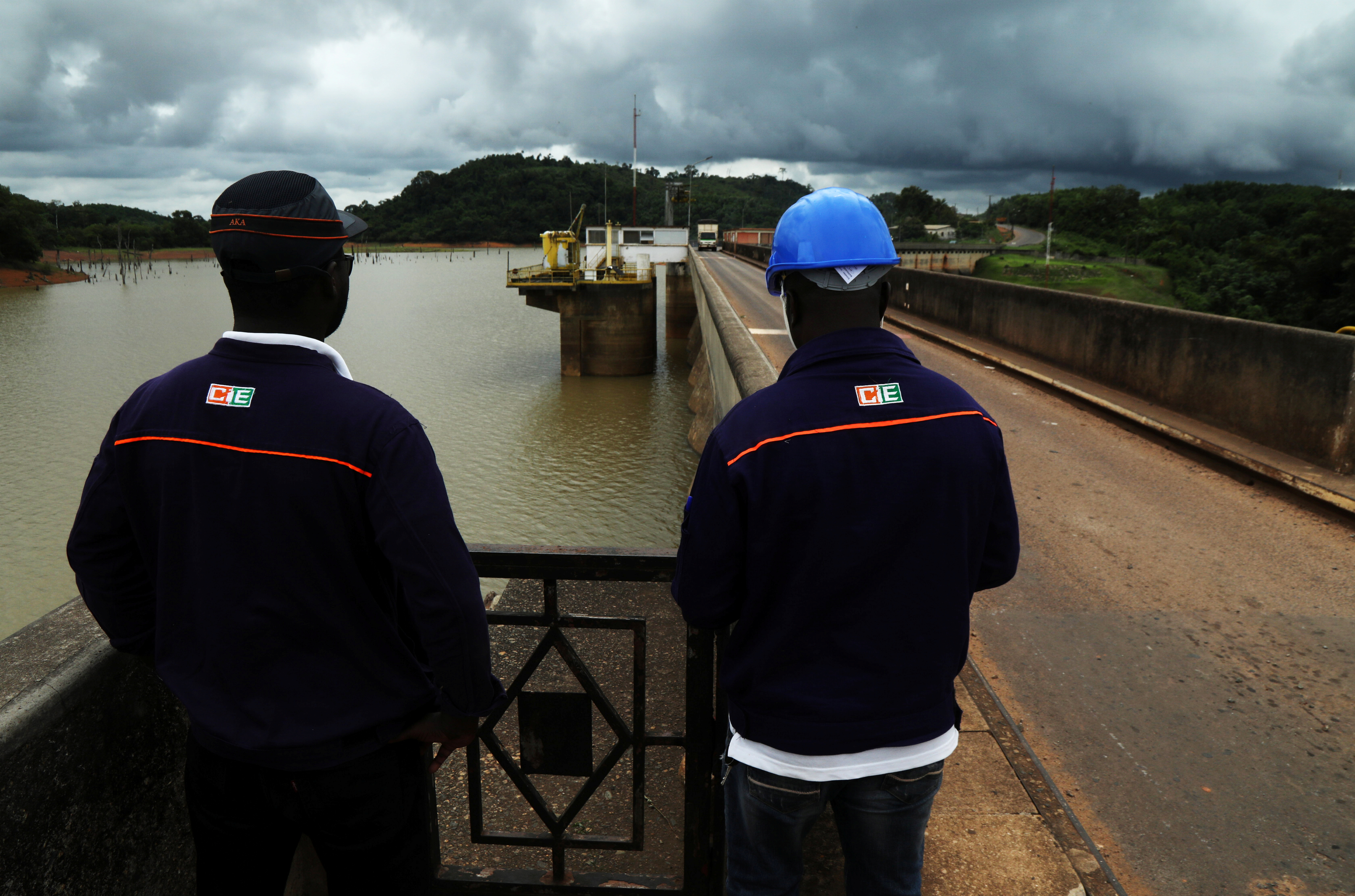 Employees of the Ivory Coast Electricity Company (CIE) examine the level of a river, which has fallen due to dry season, upstream of a hydroelectric dam in Ayame, Ivory Coast May 6, 2021. Picture taken May 6, 2021. REUTERS/Luc Gnago