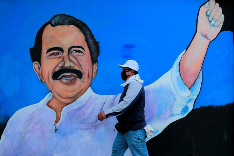 A man, wearing a face mask for protection against the coronavirus disease (COVID-19), walks by a mural depicting Nicaraguan President Daniel Ortega, in Managua, Nicaragua March 30, 2020. Picture taken March 30, 2020. REUTERS/Oswaldo Rivas/File Photo