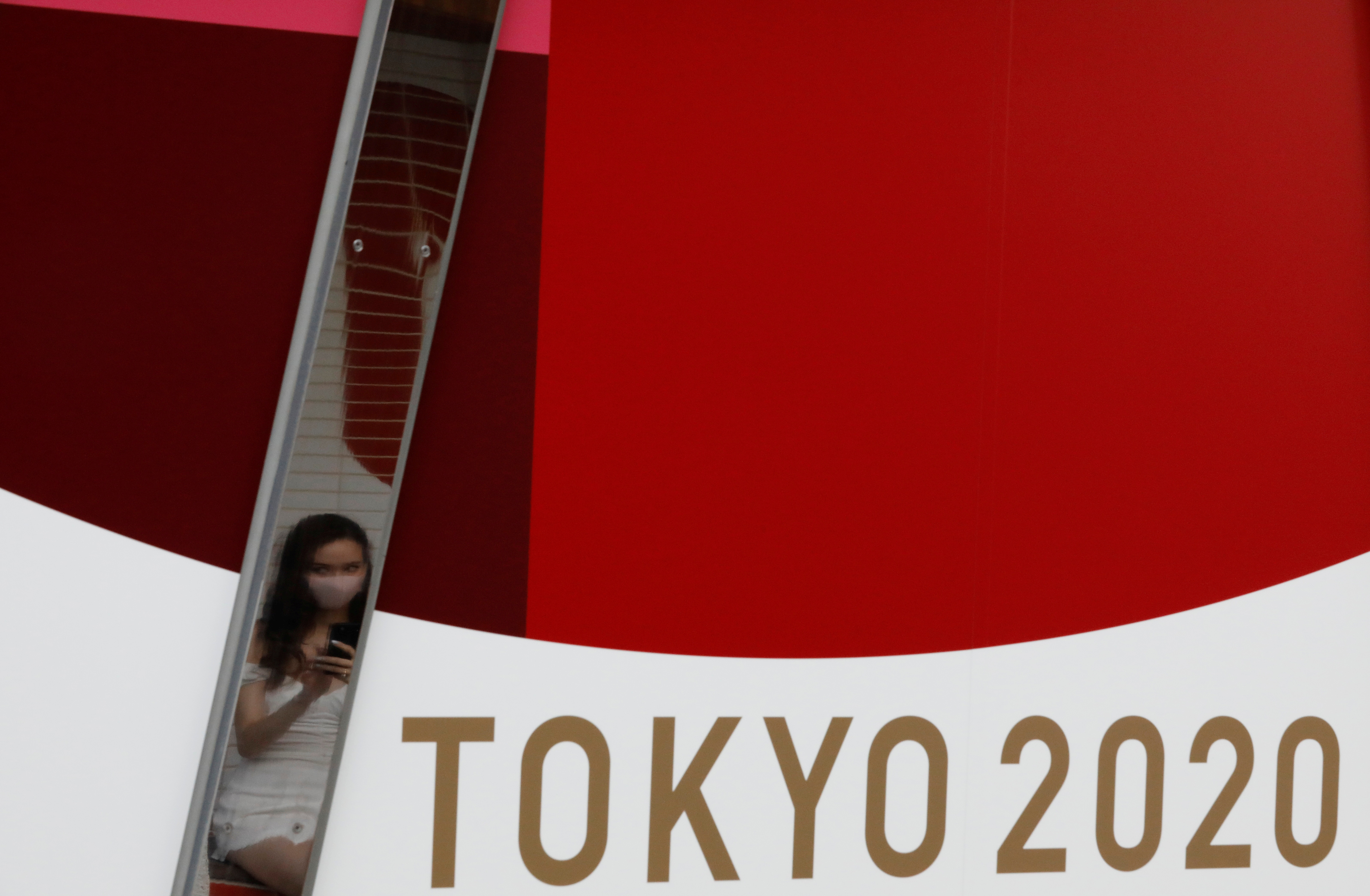 A woman wearing a protective mask, following the coronavirus disease (COVID-19) outbreak, is reflected on a metal bar on an advertisement for Tokyo 2020 Olympic Games in Tokyo, Japan, July 7, 2021.   REUTERS/Kim Kyung-Hoon/
