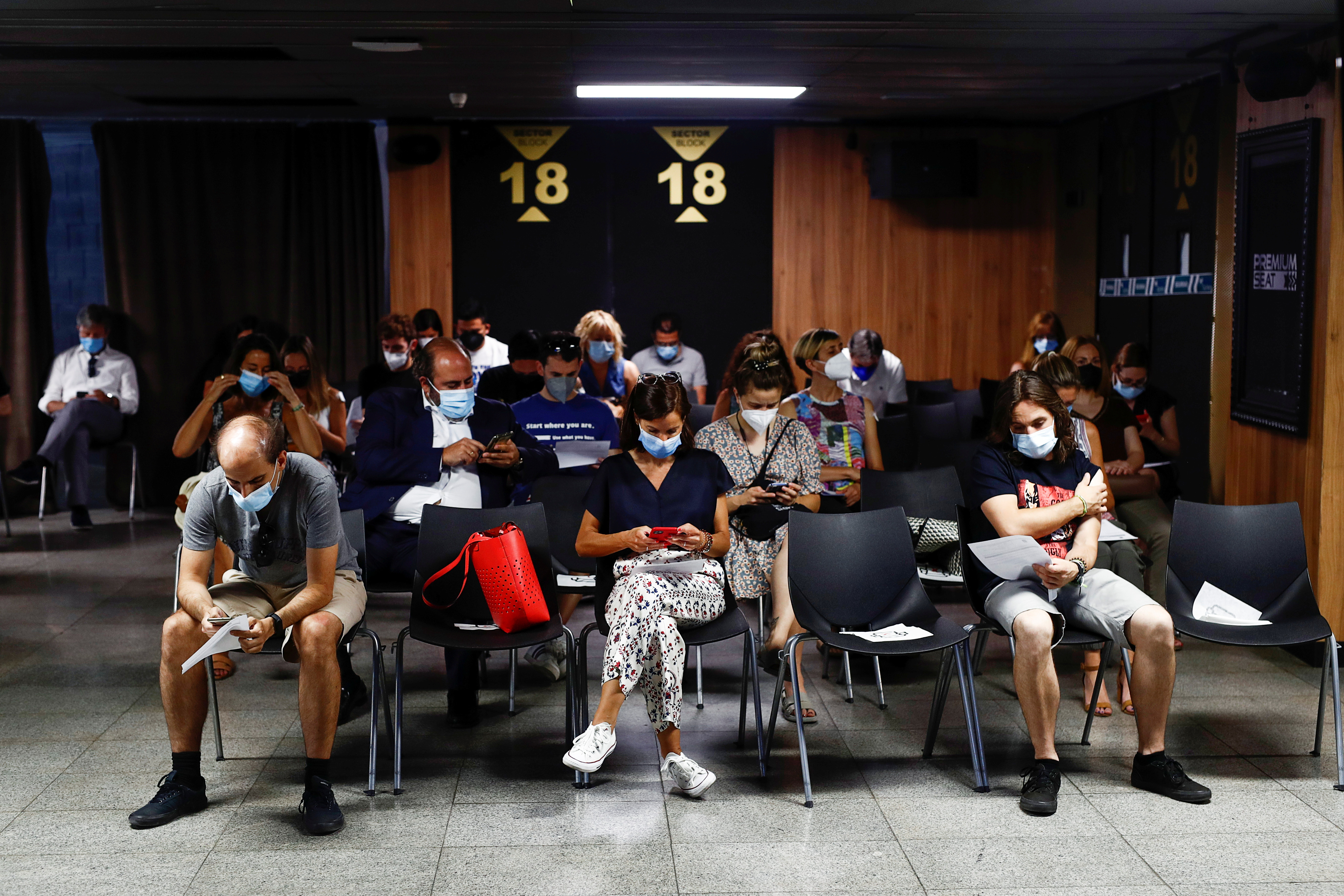 People sit after they received a coronavirus disease (COVID-19) vaccine as the country extends vaccination to curb surge among population under 30, in Madrid, Spain, July 12, 2021. REUTERS/Javier Barbancho