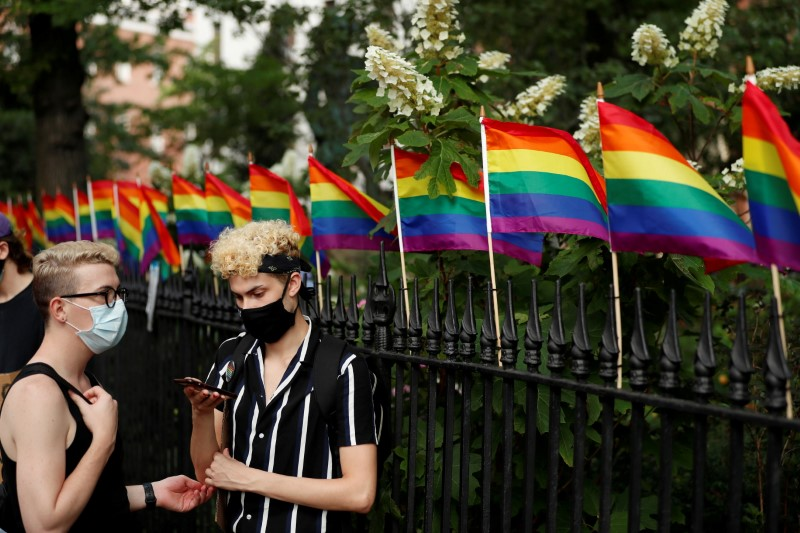 Demonstrators take a moment while listening to speakers voice their support for gay pride and black lives matter movements in New York City, New York, U.S., June 25, 2020. REUTERS/Lucas Jackson/File Photo