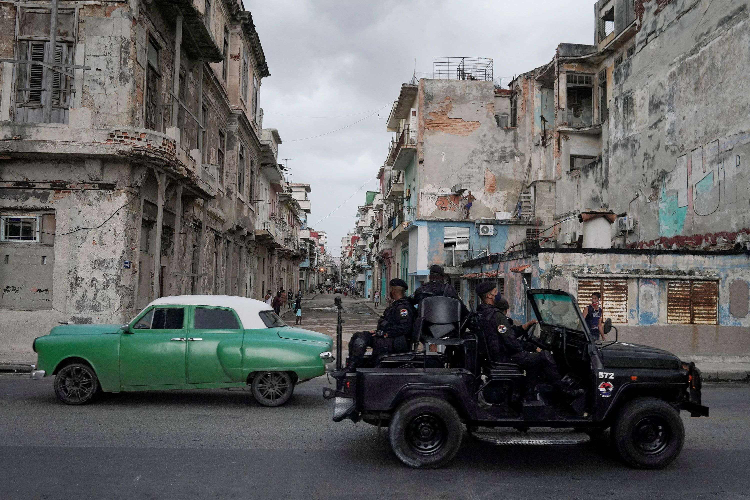 A special forces vehicle passes by a vintage car in downtown Havana, Cuba, July 13, 2021. REUTERS/Alexandre Meneghini