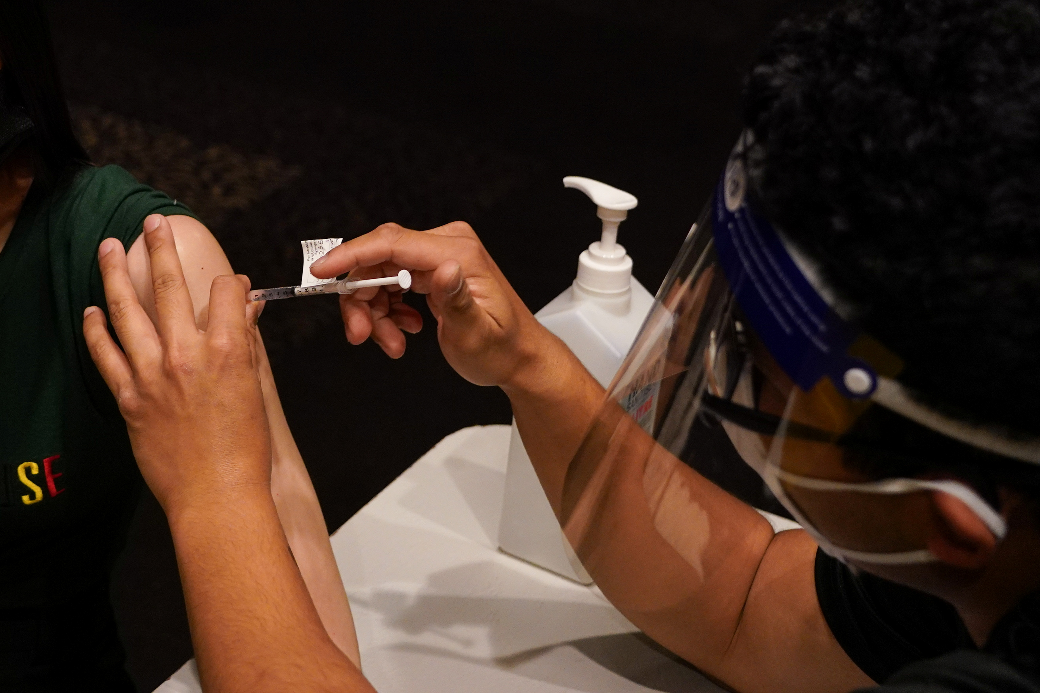 A patient receives the AstraZeneca vaccine administered by a nurse immuniser at a coronavirus disease (COVID-19) vaccination clinic at the Bankstown Sports Club as the city experiences an extended lockdown, in Sydney, Australia, August 3, 2021.  REUTERS/Loren Elliott