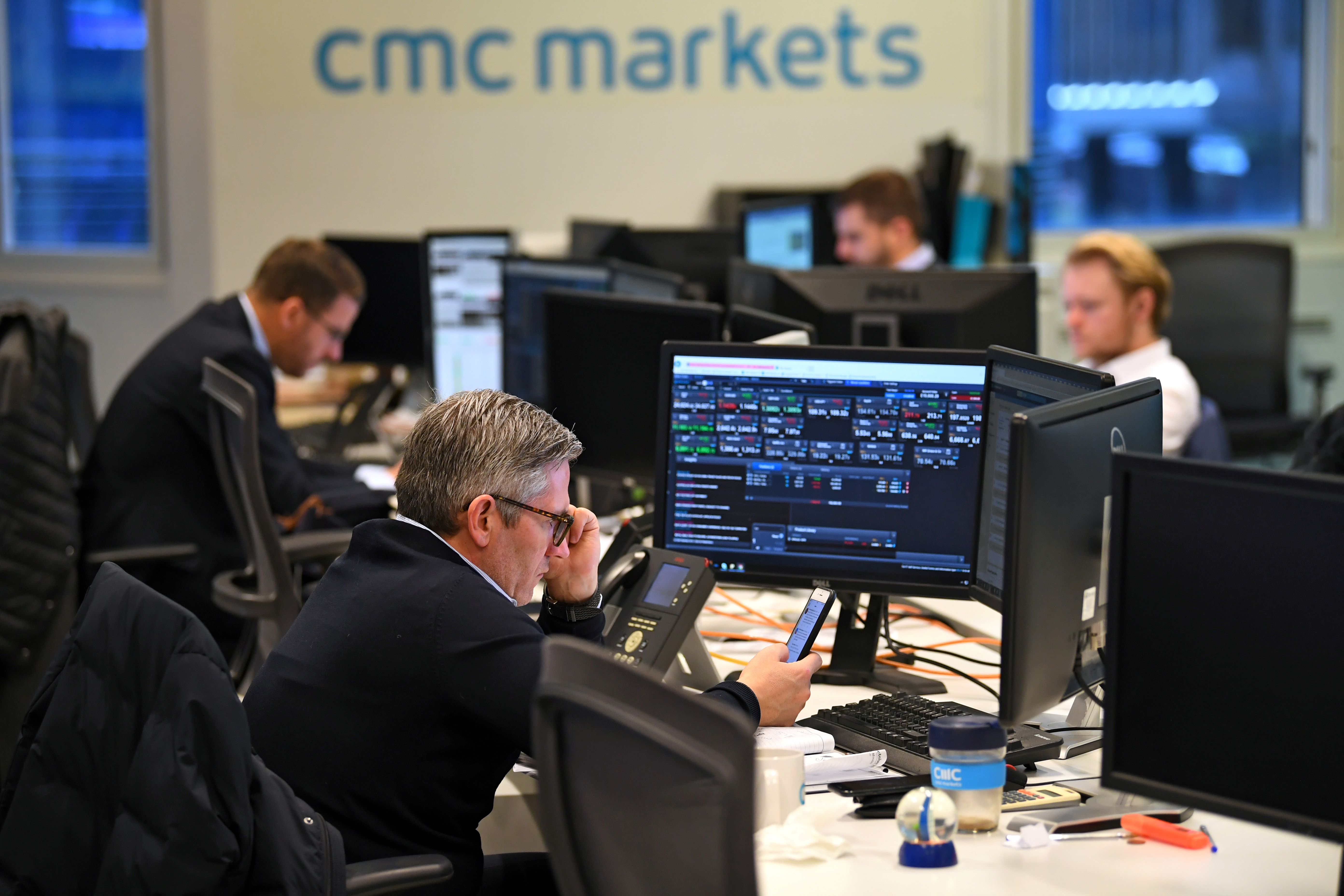 Dealers work at their desks whilst screens show market data at CMC Markets in London, Britain, January 30, 2019. REUTERS/Dylan Martinez/File Photo