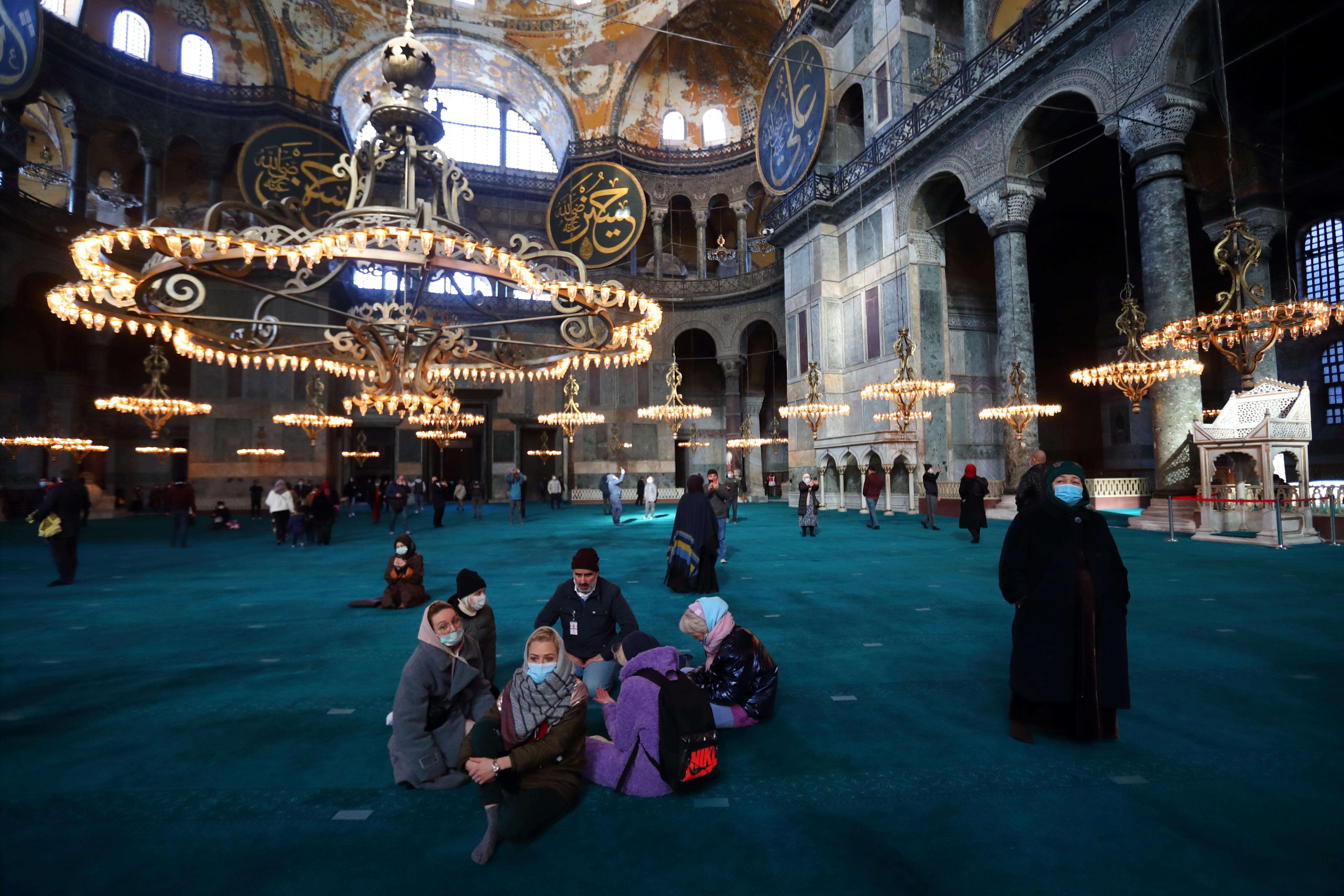 Russian tourists pause as they visit Ayasofya-i Kebir Camii or Hagia Sophia Grand Mosque amid the coronavirus disease (COVID-19) outbreak in Istanbul, Turkey January 29, 2021. REUTERS/Murad Sezer/Files