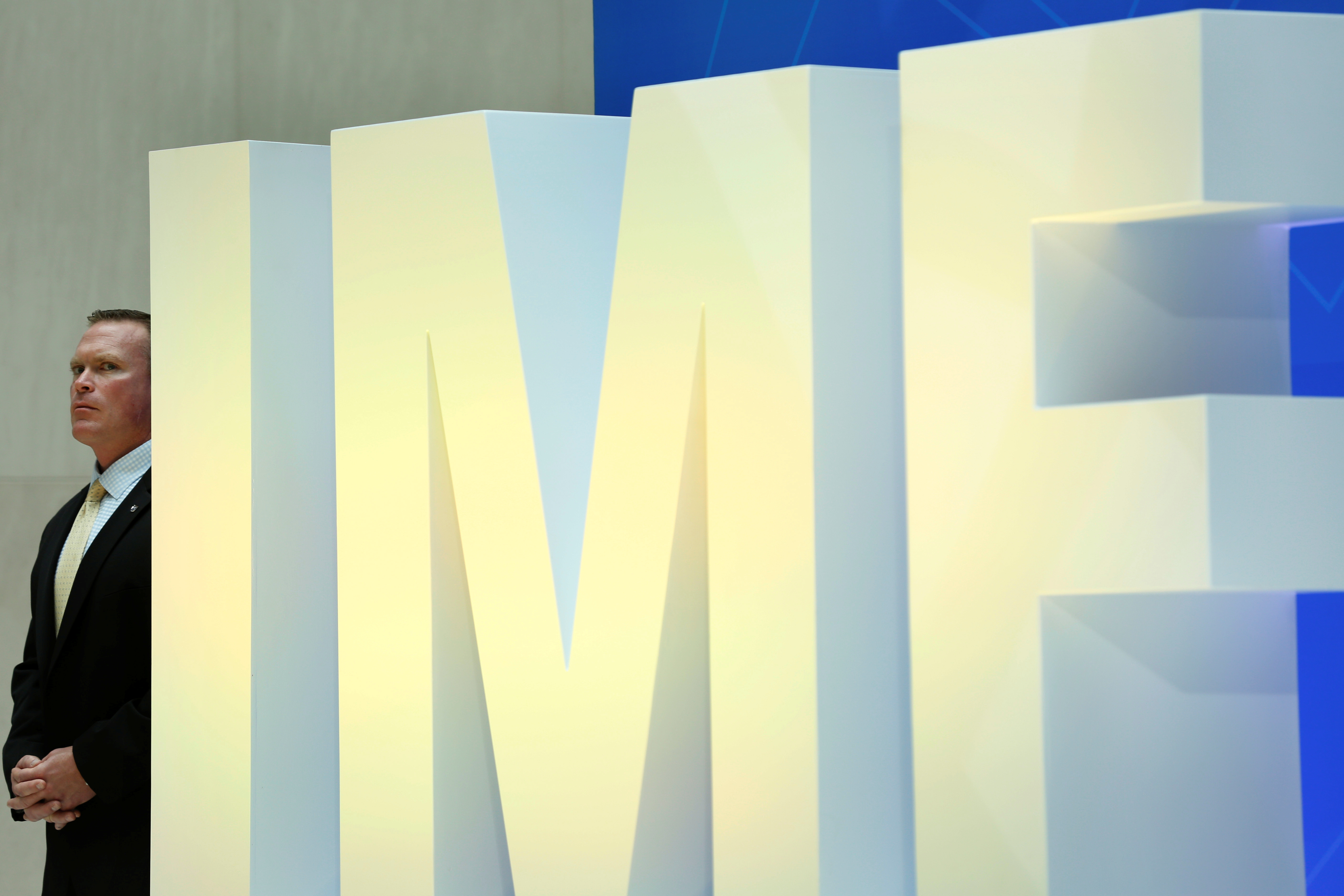 A security personnel stands next to International Monetary Fund logo at IMF headquarters in Washington, U.S., April 19, 2017. REUTERS/Yuri Gripas