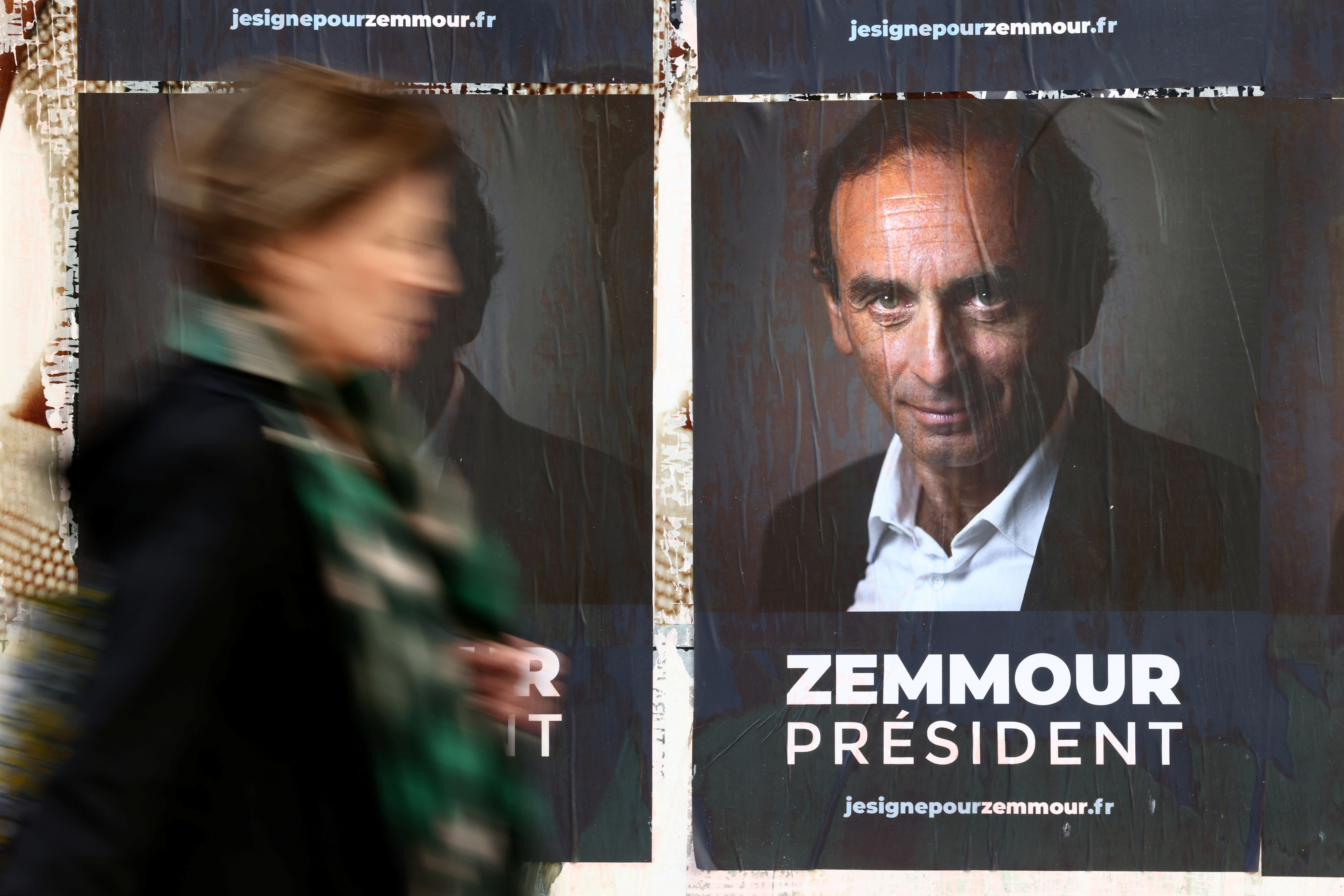 A woman walks past posters in support of French far-right commentator Eric Zemmour, probable candidate for the French presidential election next April, posted on a wall in Paris, France, October 13, 2021. The slogan reads