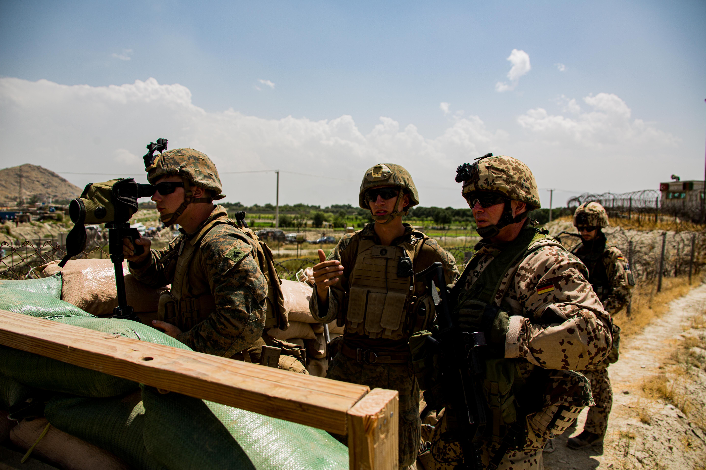 U.S. Marines and German service member watch an entry gate during an evacuation at Hamid Karzai International Airport, Kabul, Afghanistan, August 28, 2021.  U.S. Marine Corps/Cpl. Davis Harris/Handout via REUTERS