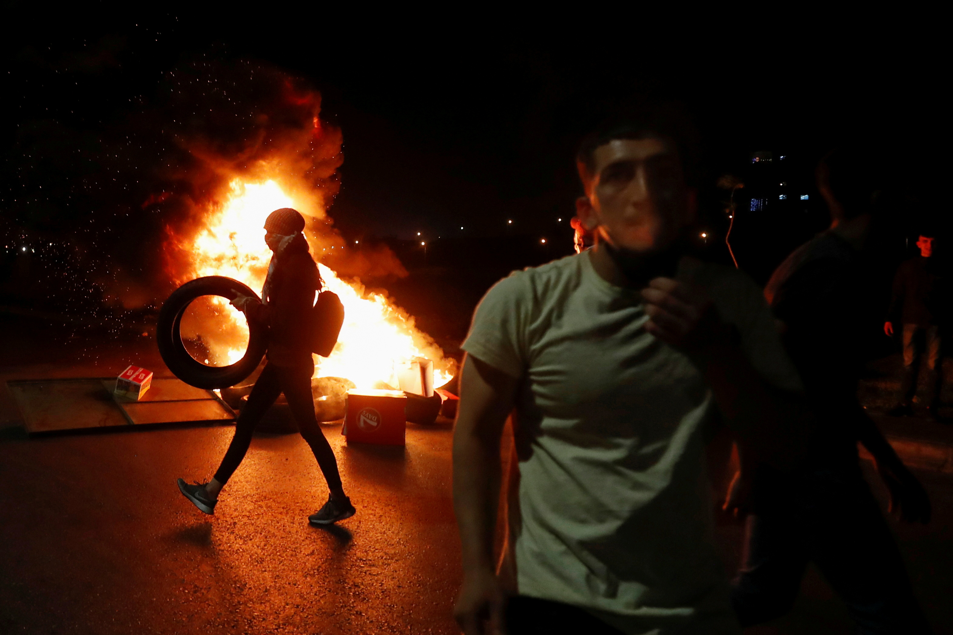 A Palestinian woman demonstrator carries a tire as she walks past a burning barricade during an anti-Israel protest over tension in Jerusalem, near the Jewish settlement of Beit El near Ramallah, in the Israeli-occupied West Bank May 9, 2021. REUTERS/Mohamad Torokman