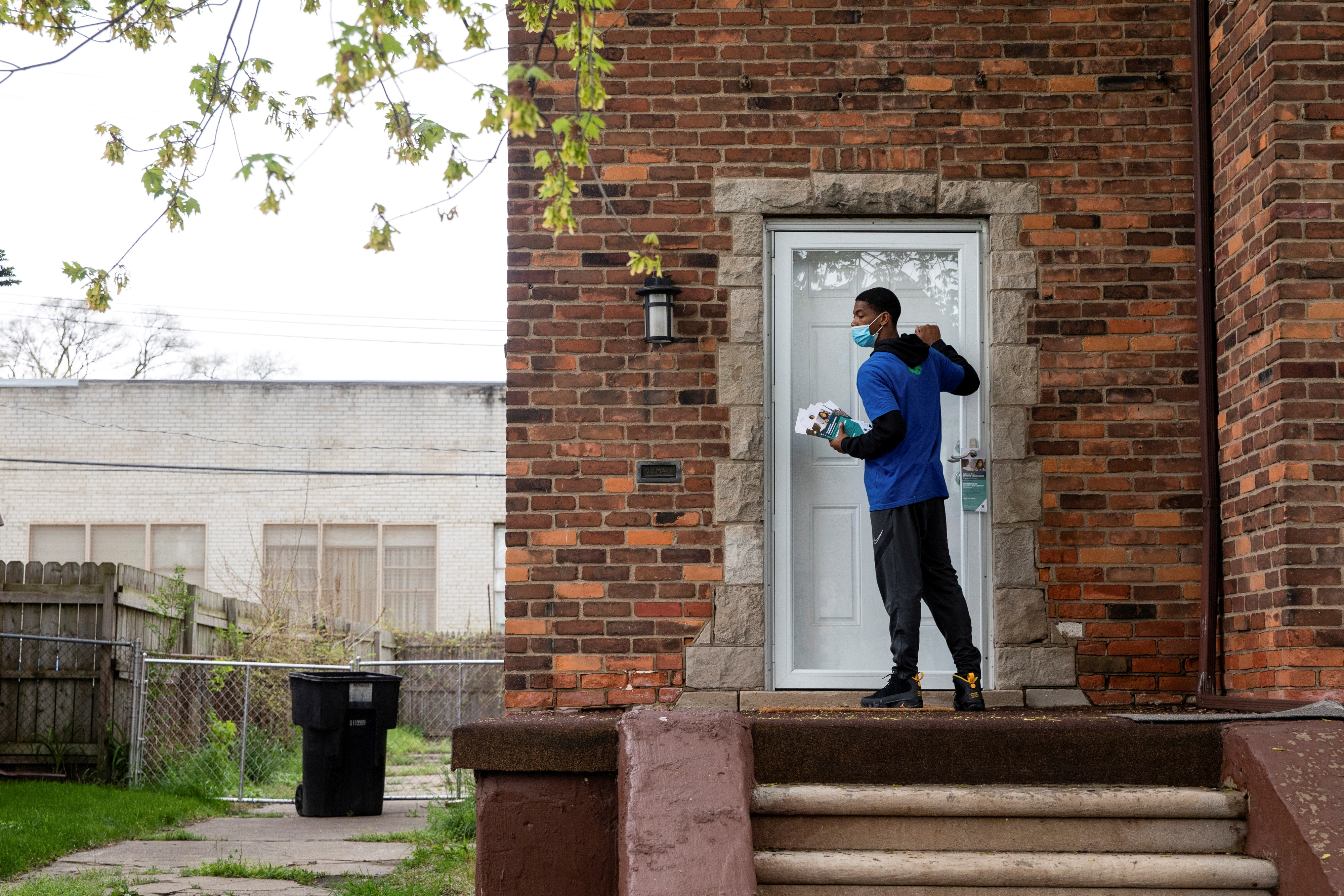 Sirgregory Allen from Better Men Outreach knocks on doors during a door-knock campaign to provide information about where people can get their vaccinations and answer questions related to hesitancy around the coronavirus disease (COVID-19) vaccine in Detroit, Michigan, U.S., May 4, 2021. REUTERS/Emily Elconin     TPX IMAGES OF THE DAY - RC2Z8N93JI0C