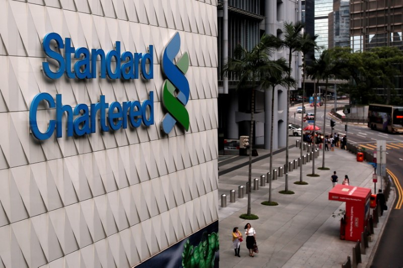 People walk outside the main branch of Standard Chartered in Hong Kong, China August 1, 2017. REUTERS/Bobby Yip/File Photo