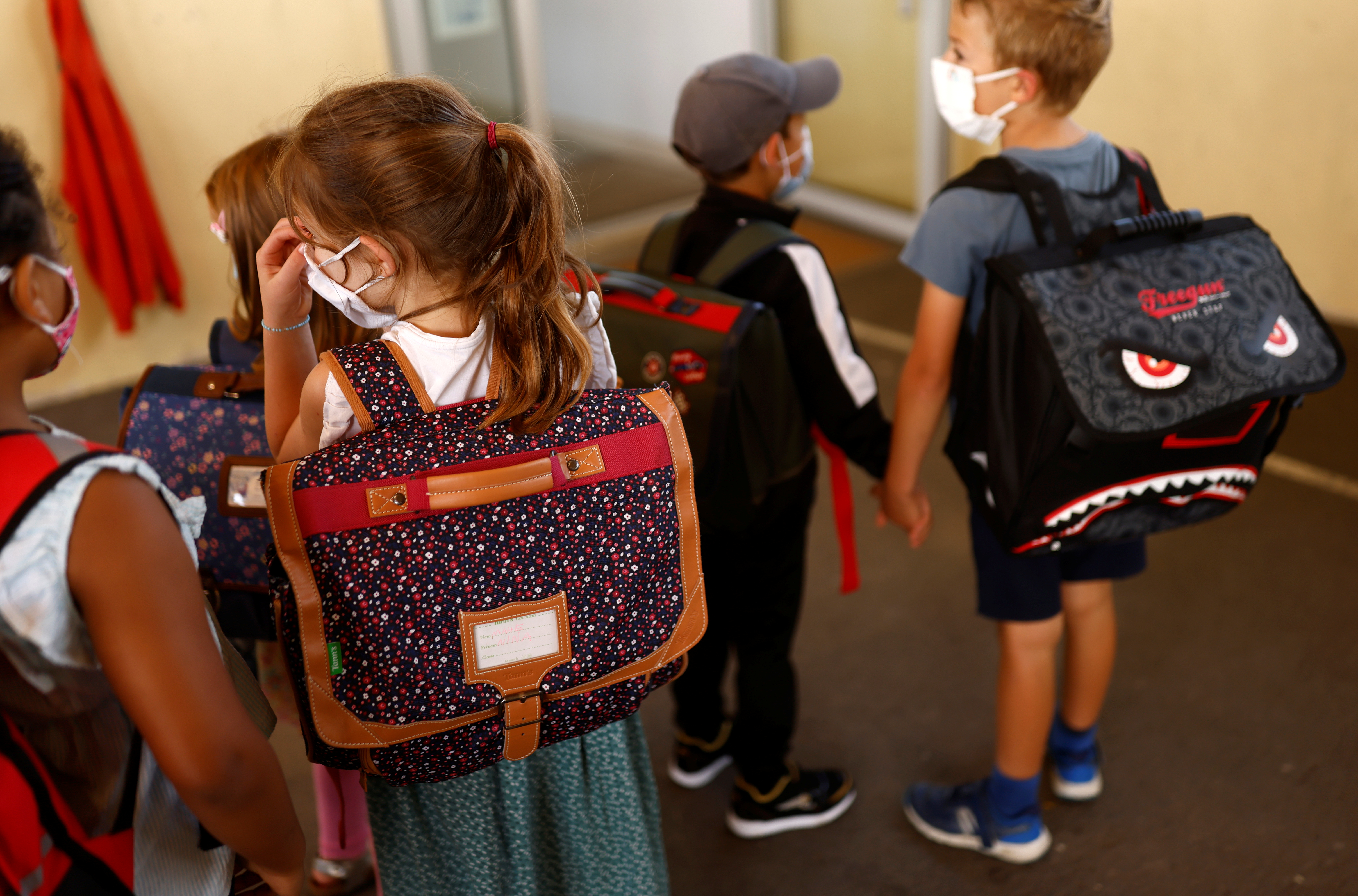 Schoolchildren, wearing protective face masks, gather as they arrive at a primary school on the first day of the new school year after summer break, in Vertou, France, September 2, 2021. REUTERS/Stephane Mahe