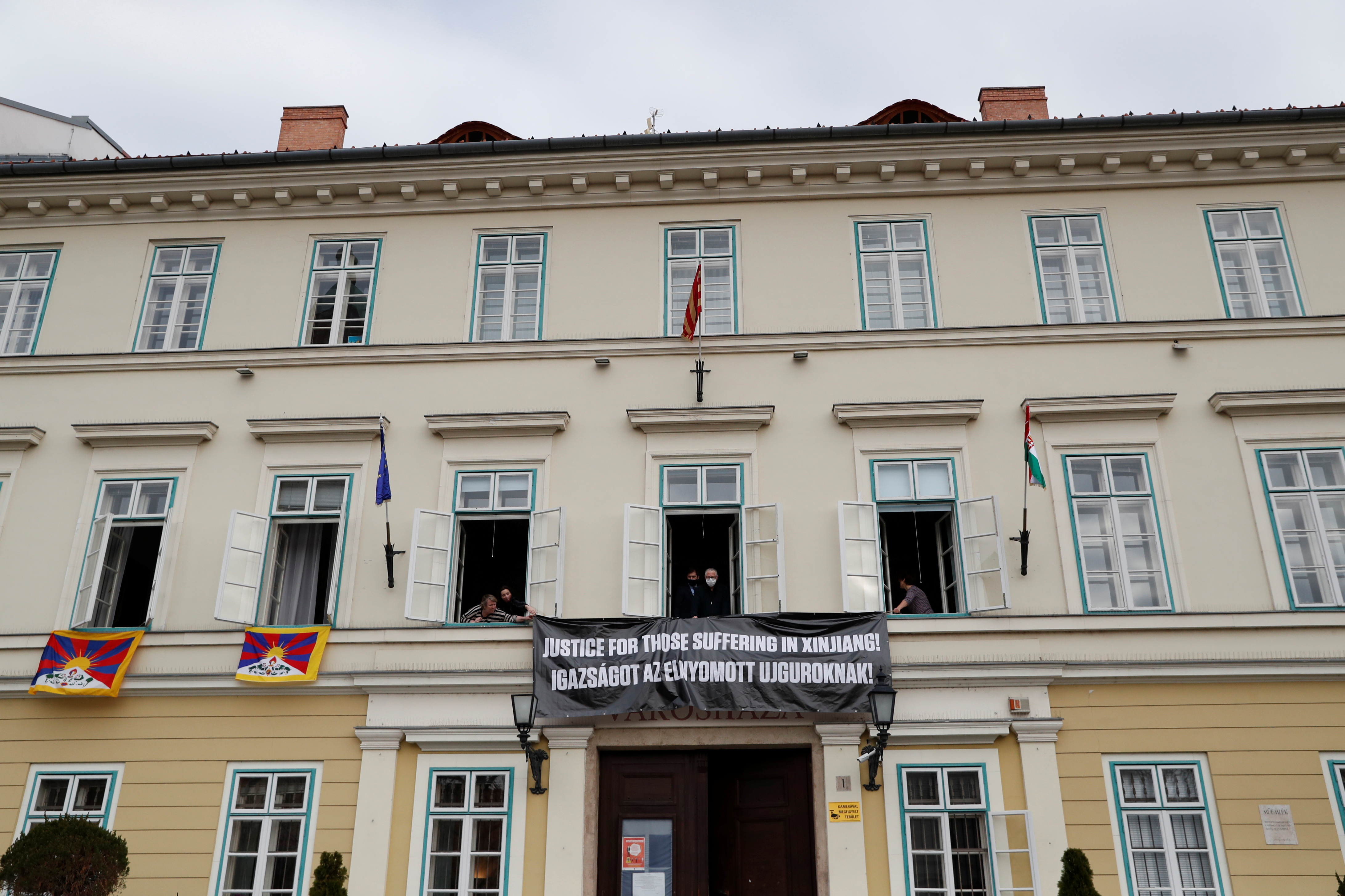 Hungarian opposition members hang a banner outside the District Mayor?s Office building during the visit of Chinese Defence Minister Wei Fenghe, to protest over China's treatment of Uighurs, in Budapest, Hungary, March 25, 2021. REUTERS/Bernadett Szabo