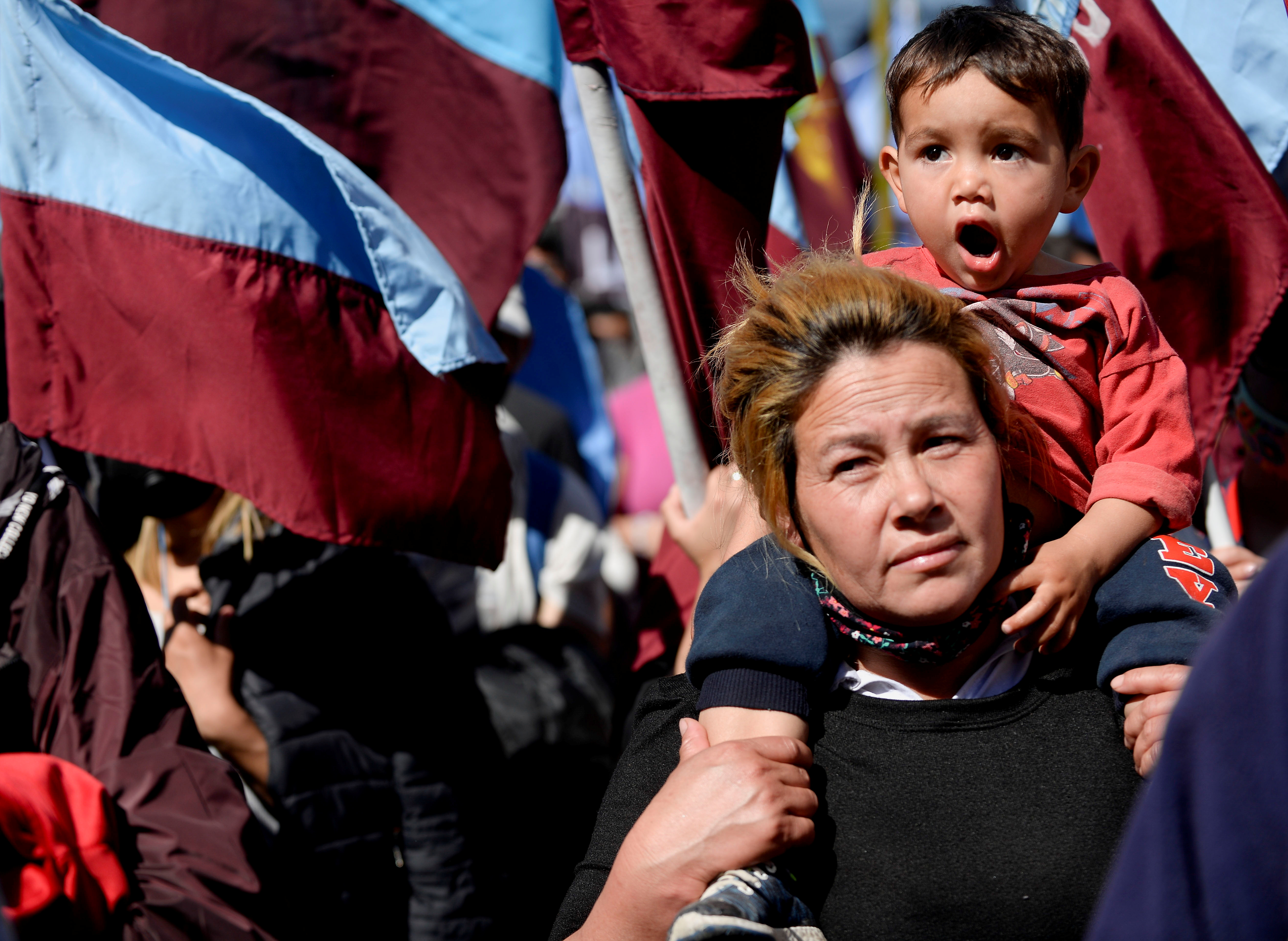 A mother carries her son as they march to protest against unemployment, food insecurity and lack of resources, in Buenos Aires, Argentina September 16, 2021.  REUTERS/Mariana Nedelcu