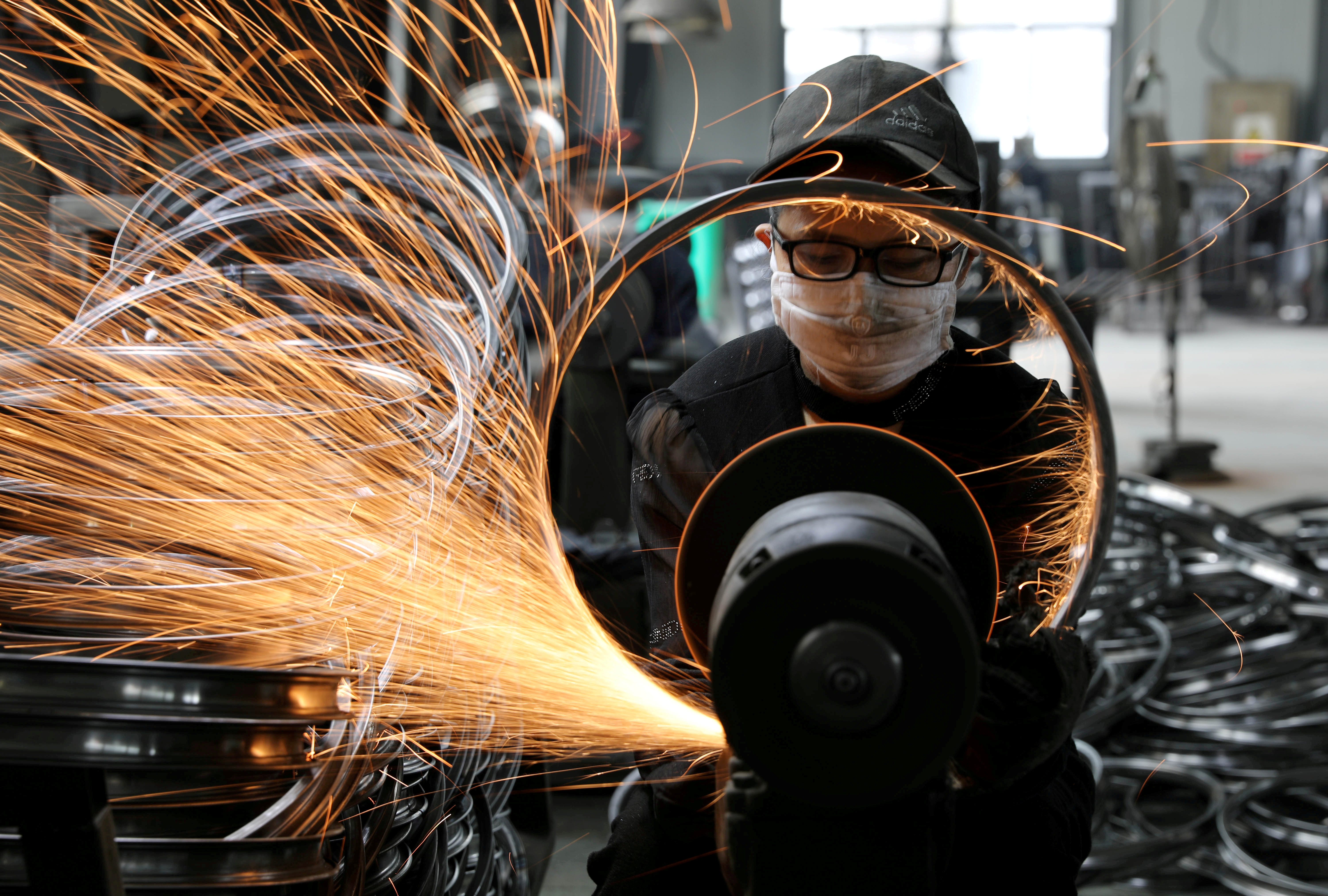 A worker welds a bicycle steel rim at a factory manufacturing sports equipment in Hangzhou, Zhejiang province, China September 2, 2019. China Daily via REUTERS/File Photo