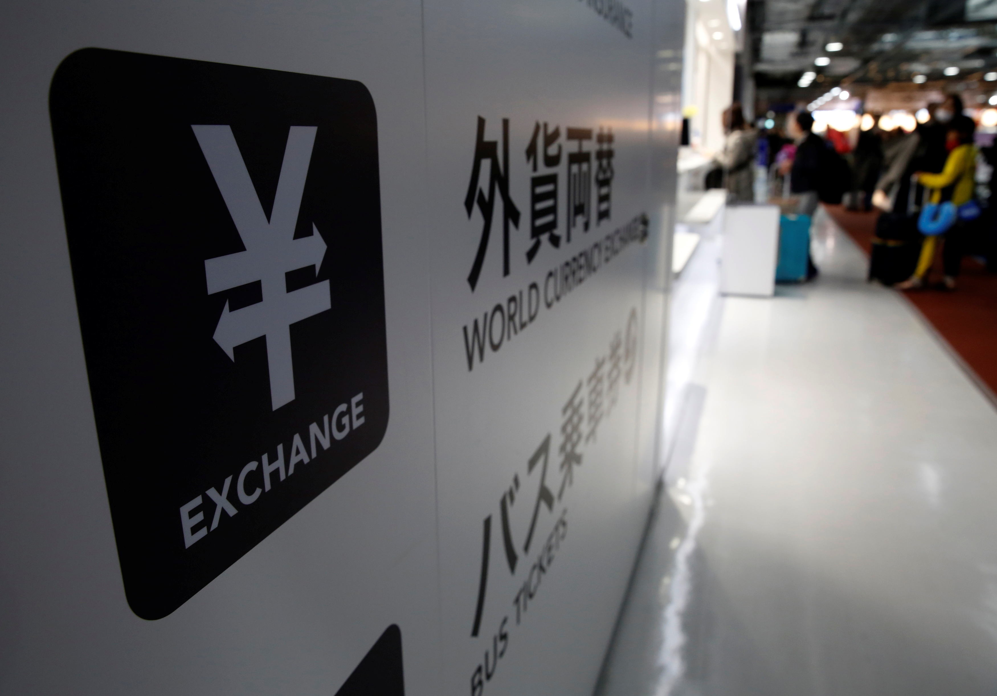 A Japanese yen currency sign (L) is seen at a currency exchange office as people line up to exchange money at Narita International airport, near Tokyo, Japan, March 25, 2016. REUTERS/Yuya Shino/File Photo