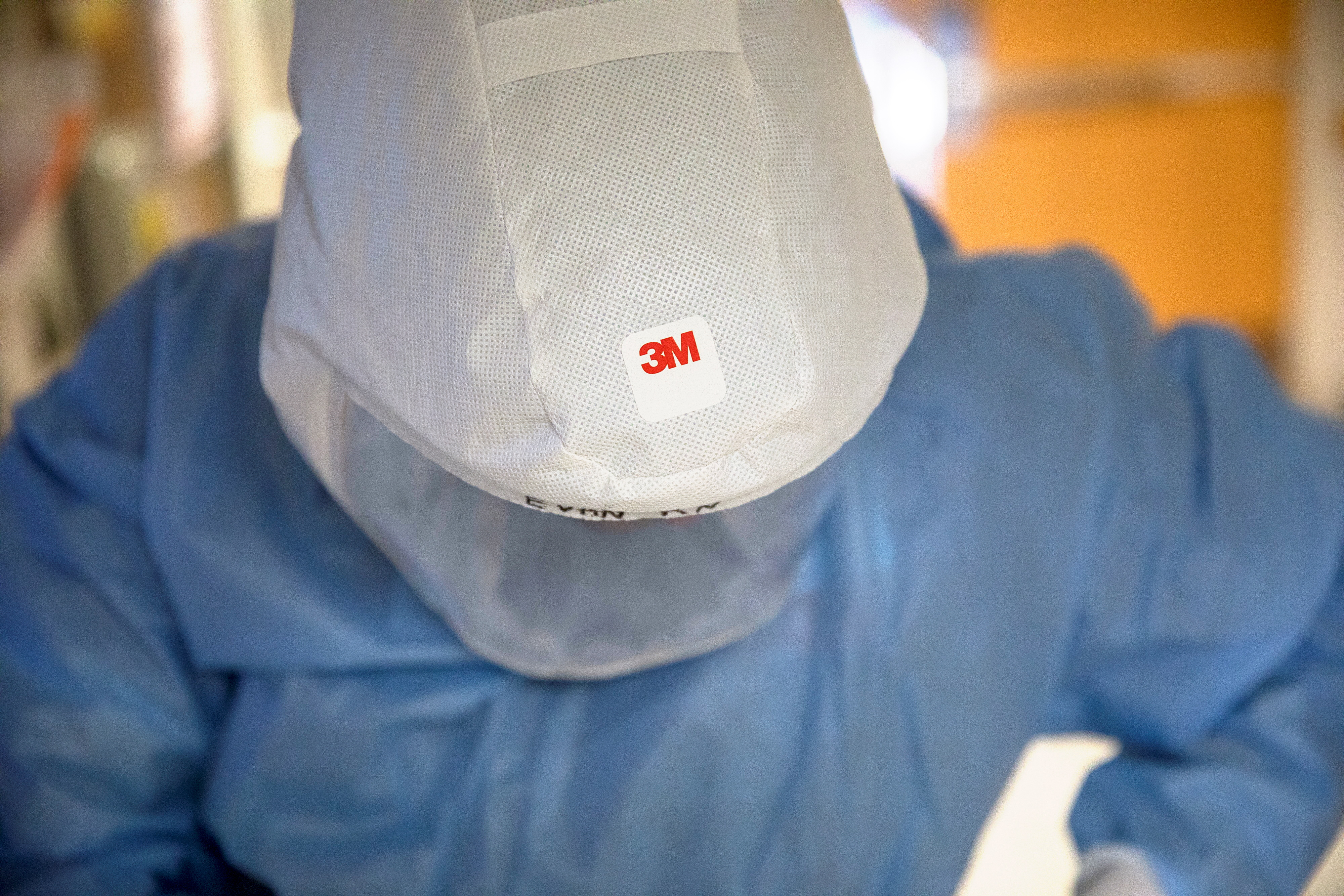 A 3M logo is seen atop a Versaflo TR-300+ powered air purifying respirator hood as Nurse Evan Brost puts on personal protective equipment (PPE) before entering a patient room in a wing housing coronavirus disease (COVID-19) patients at UW Health University Hospital in Madison, Wisconsin, U.S. November 18, 2020.  REUTERS/Daniel Acker/Files