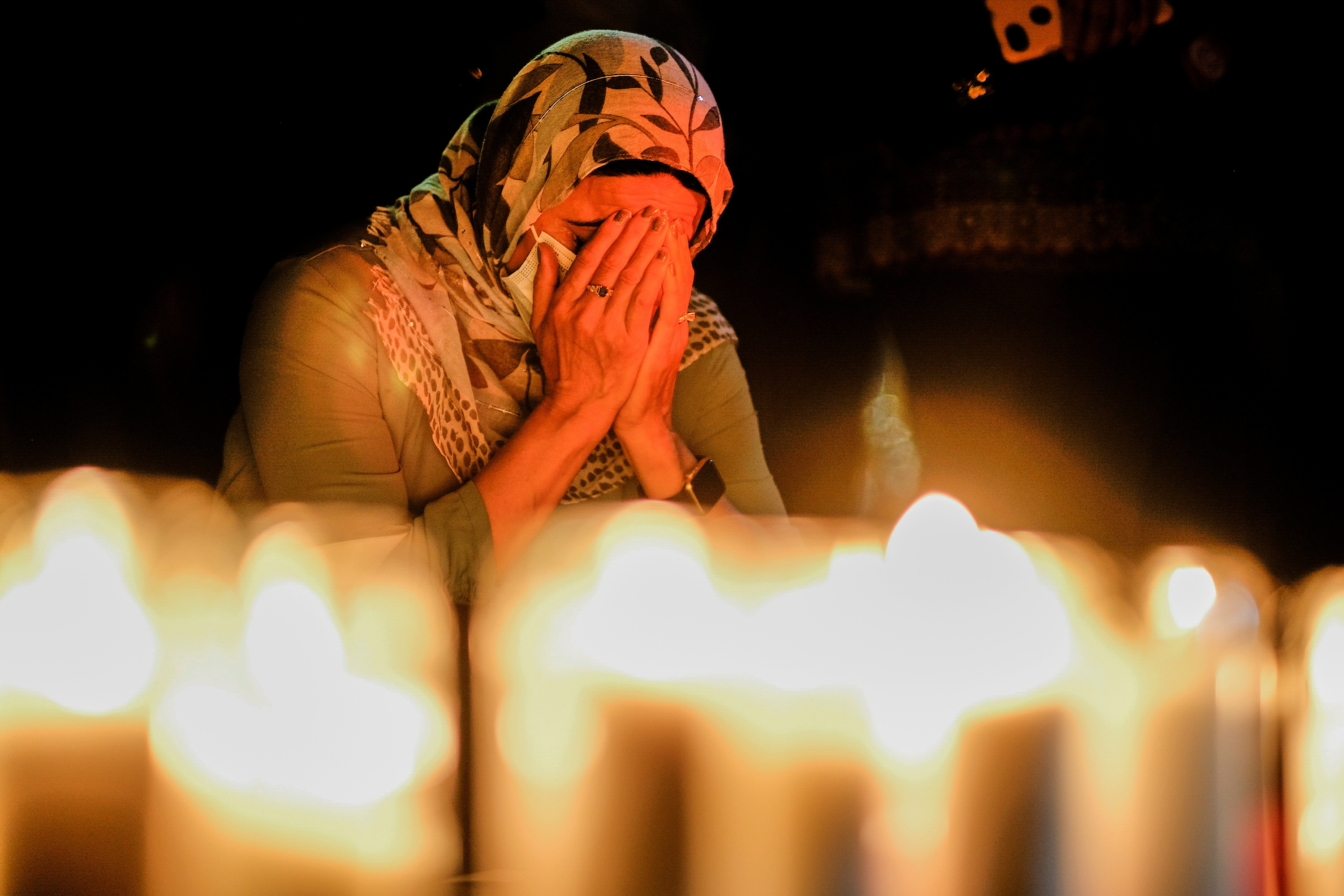A woman takes a moment in a vigil for Afghanistan outside the West LA Federal Building in Los Angeles, California, U.S. August 17, 2021.  REUTERS/Ringo Chiu     TPX IMAGES OF THE DAY