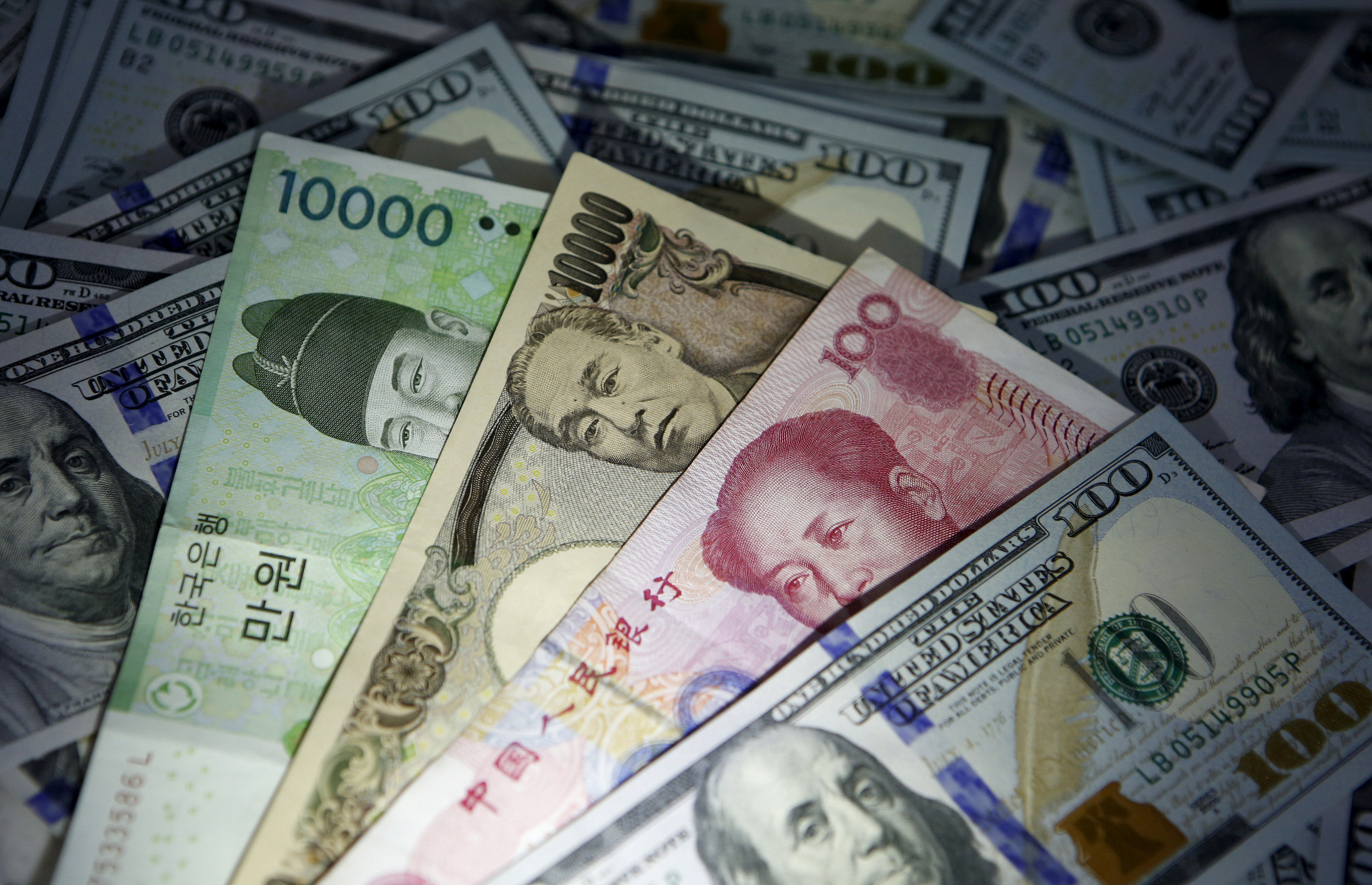 South Korean won, Chinese yuan and Japanese yen notes are seen on U.S. 100 dollar notes in this picture illustration taken in Seoul, South Korea, December 15, 2015. REUTERS/Kim Hong-Ji
