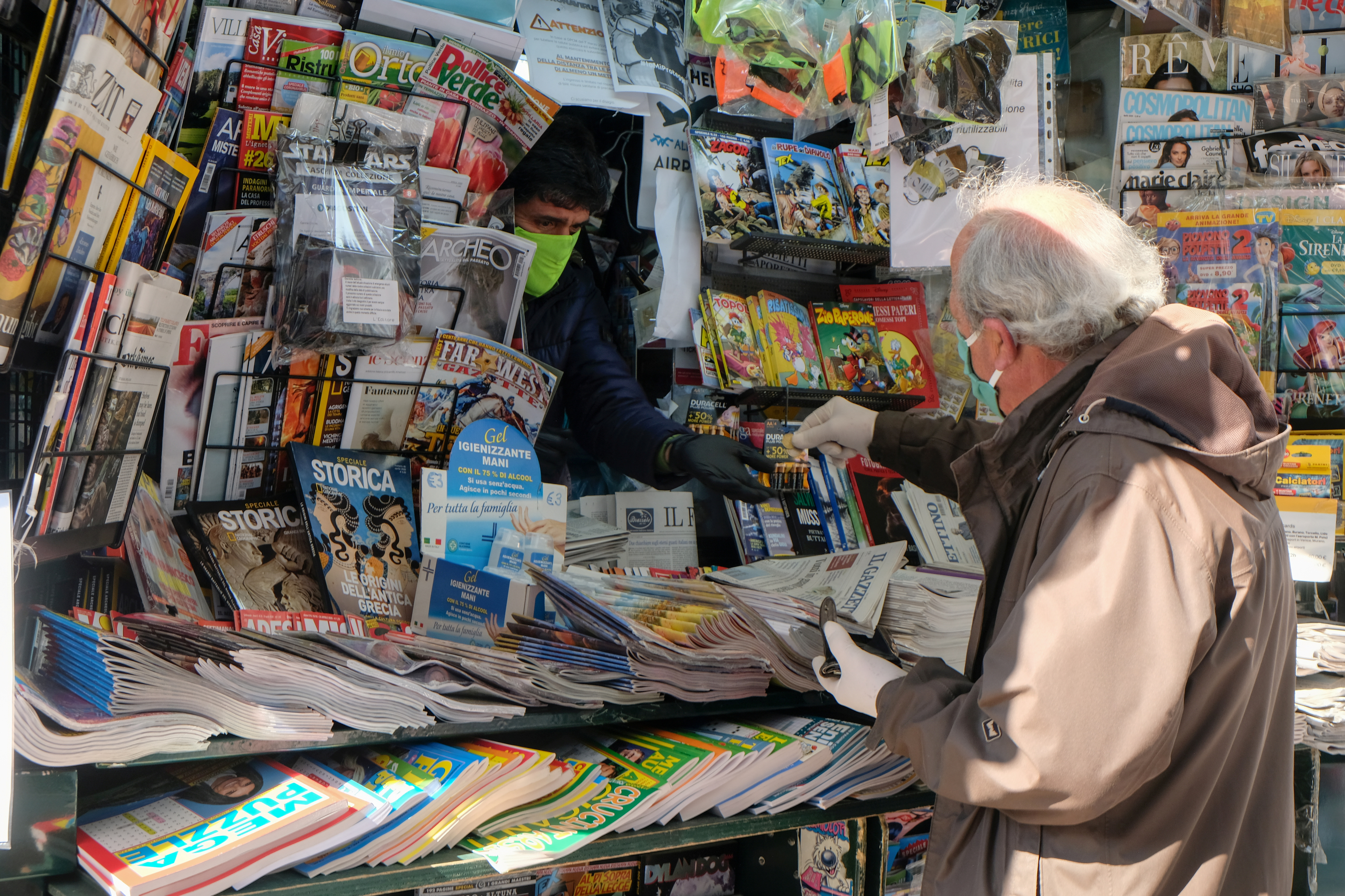 A man wears a protective face mask and gloves at the newsstand as the Italian government allows the reopening of some shops while a nationwide lockdown continues following the outbreak of the coronavirus disease (COVID-19), in Venice, Italy, April 14, 2020. REUTERS/Manuel Silvestri/File Photo