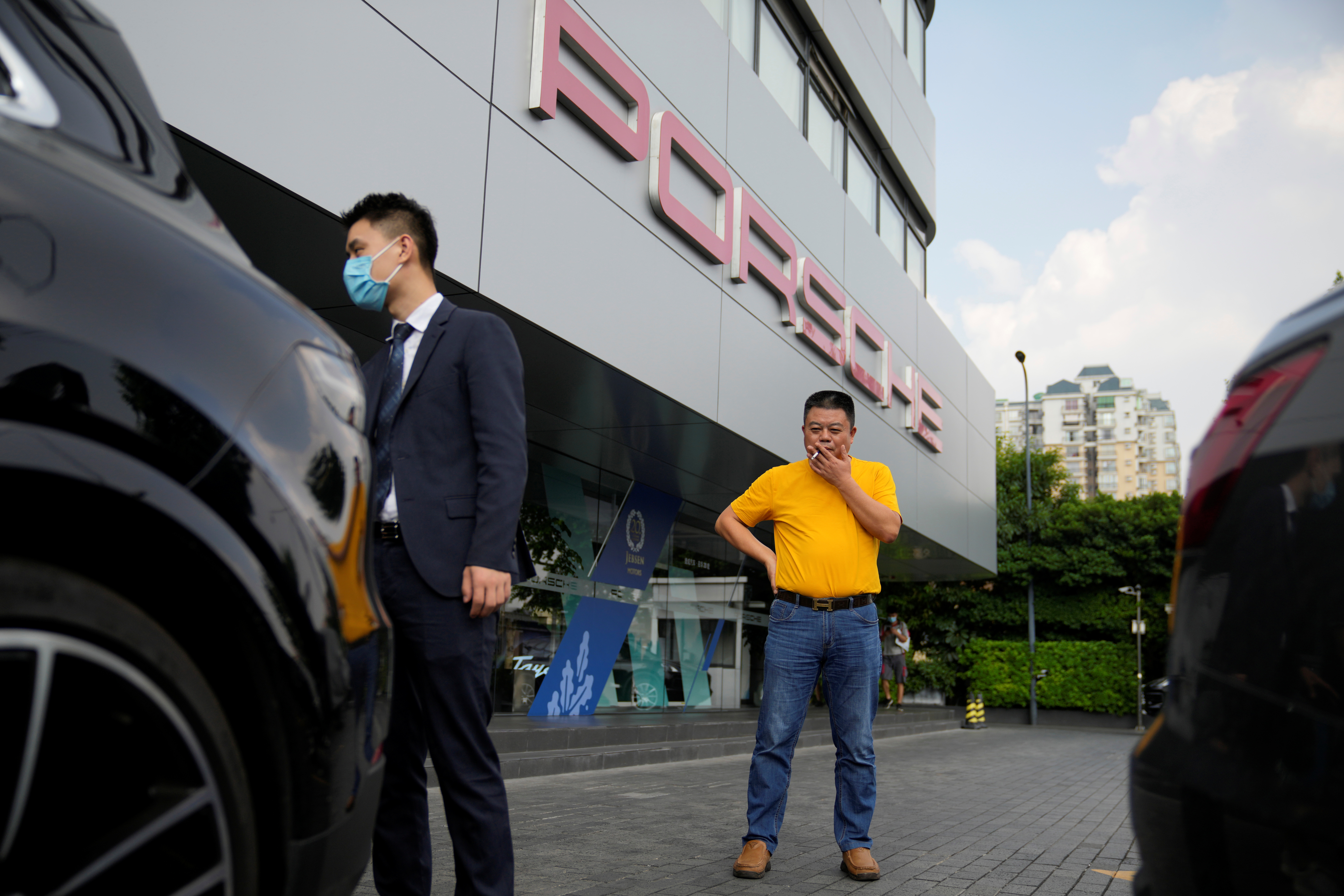 Guo Hui, whose cleaning business is owed money by China Evergrande Group, smokes a cigarette as he looks at his Porsche Cayenne he is selling to pay his debts, at a car dealership in Guangzhou, Guangdong province, China September 27, 2021. Picture taken September 27, 2021. REUTERS/Aly Song