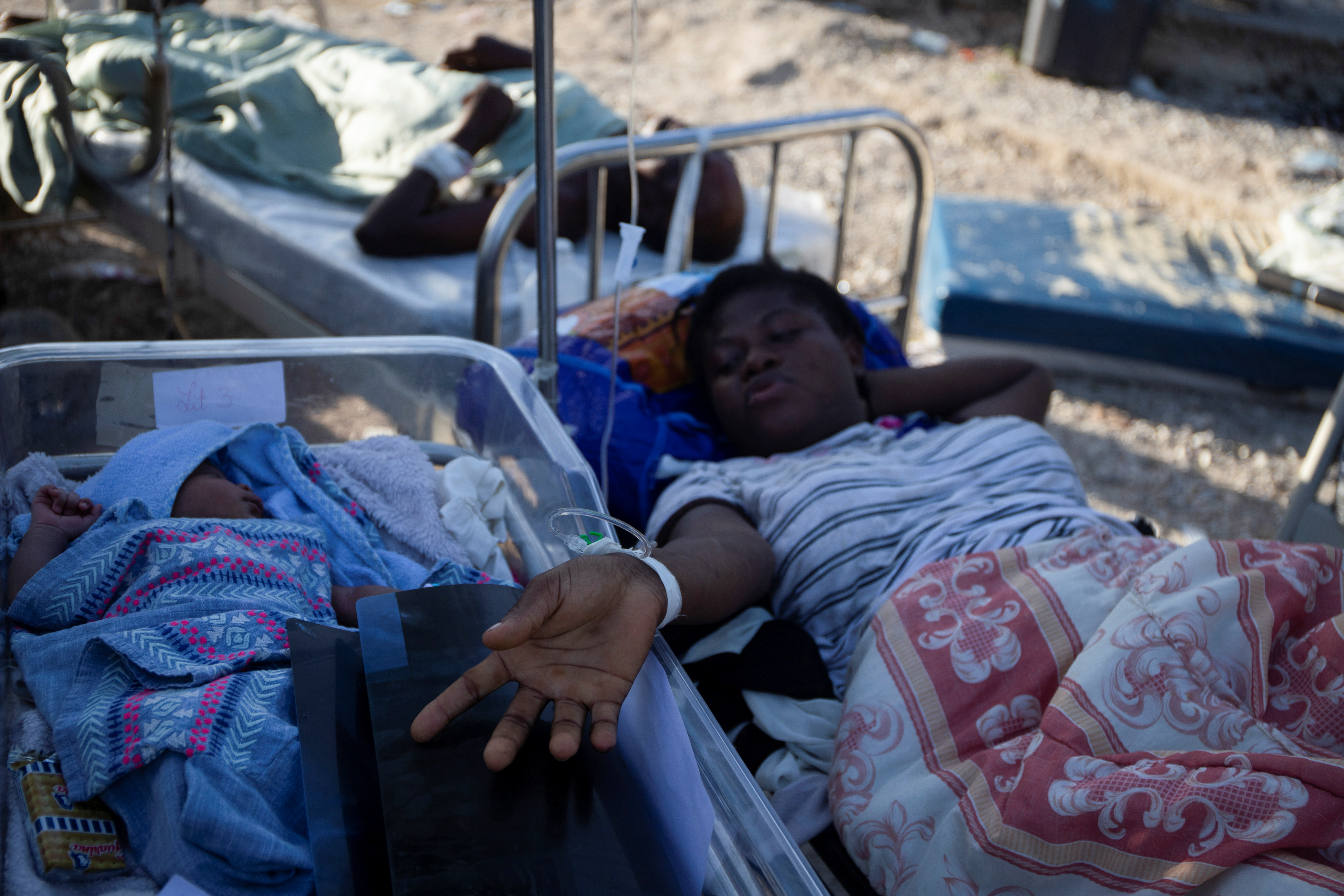 A woman on a stretcher is pictured with a baby after a 7.2 magnitude earthquake in Les Cayes, Haiti August 15, 2021.  REUTERS/Estailove St-Val
