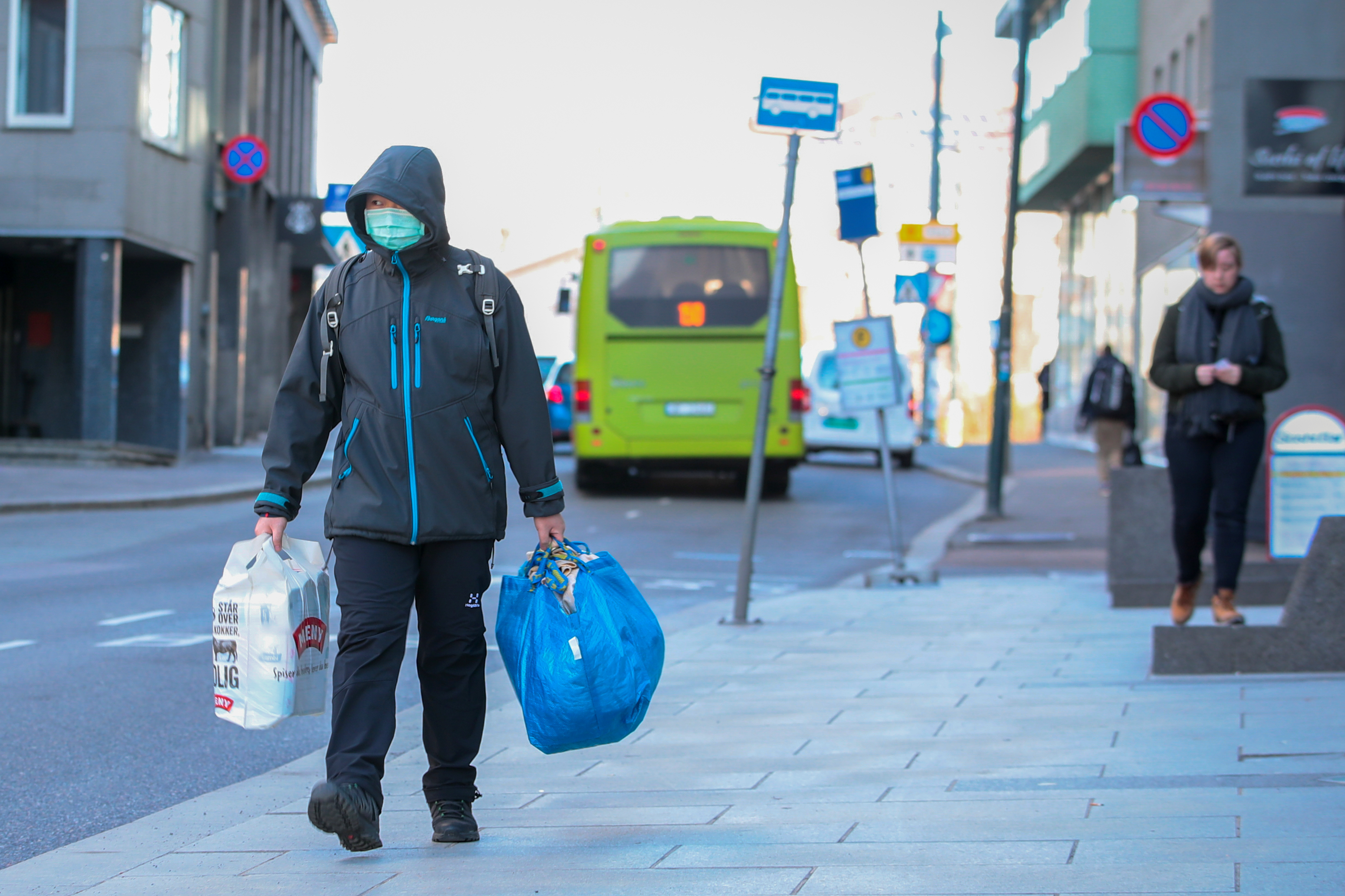 A man wearing a protective mask carries shopping bags as he walks on the streets of Oslo following an outbreak of the coronavirus disease (COVID-19), in Oslo, Norway March 13, 2020. NTB Scanpix/Hakon Mosvold Larsen via REUTERS