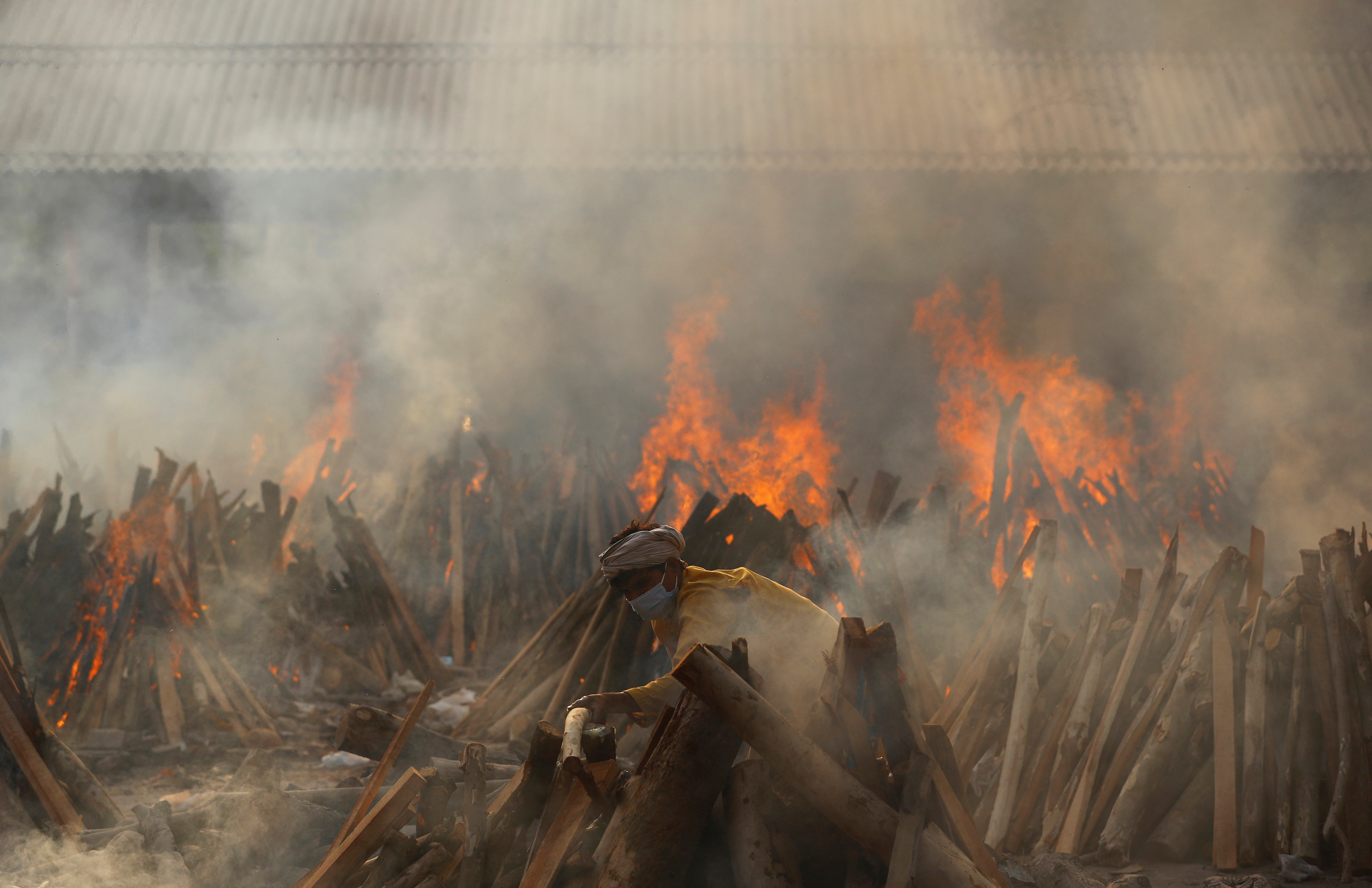 A man prepares a funeral pyre during a mass cremation of those who died from the coronavirus disease (COVID-19), at a crematorium in New Delhi, India May 1, 2021. REUTERS/Adnan Abidi