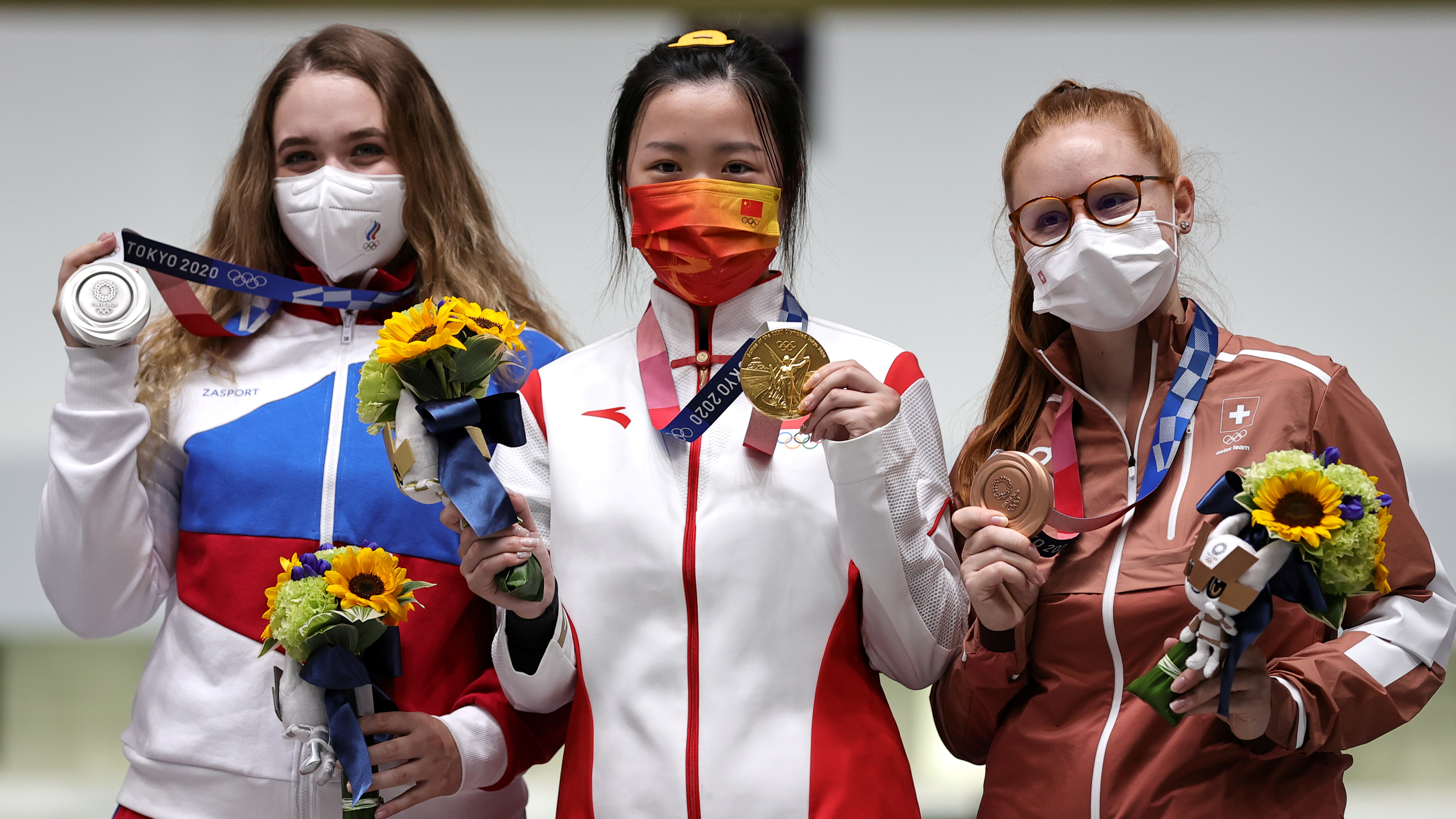 Tokyo 2020 Olympics - Shooting - Women's 10m Air Rifle - Medal Ceremony - Asaka Shooting Range, Tokyo, Japan – July 24, 2021. Gold medallist Yang Qian of China celebrates on the podium with silver medallist, Anastasiia Galashina of the Russian Olympic Committee and bronze medallist, Nina Christen of Switzerland REUTERS/Ann Wang