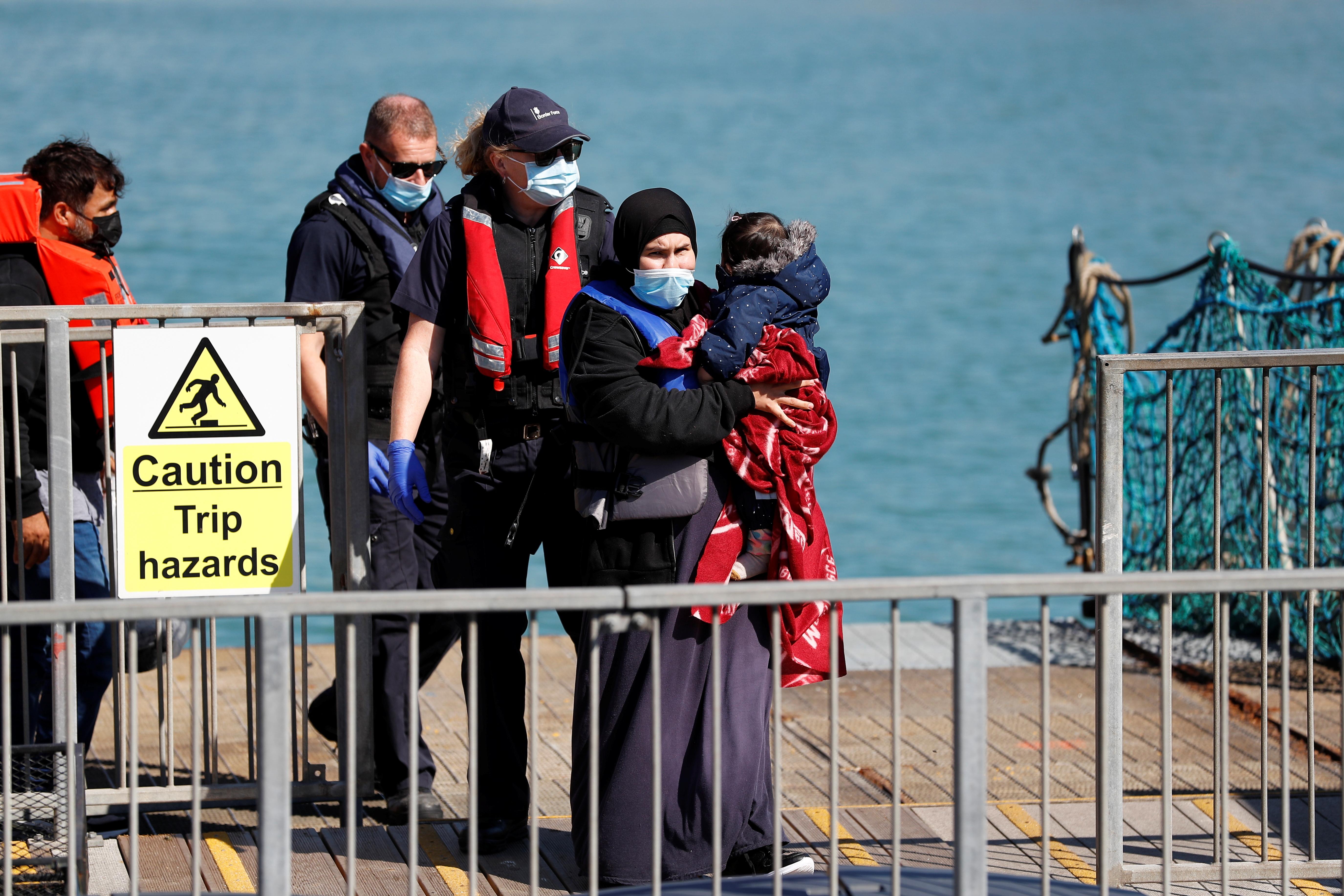İngilis Kanalından xilas edilən bir miqrant, 8 sentyabr 2021 -ci ildə İngiltərənin Dover şəhərində bir uşağı tutaraq gəzir. REUTERS/Peter Nicholls