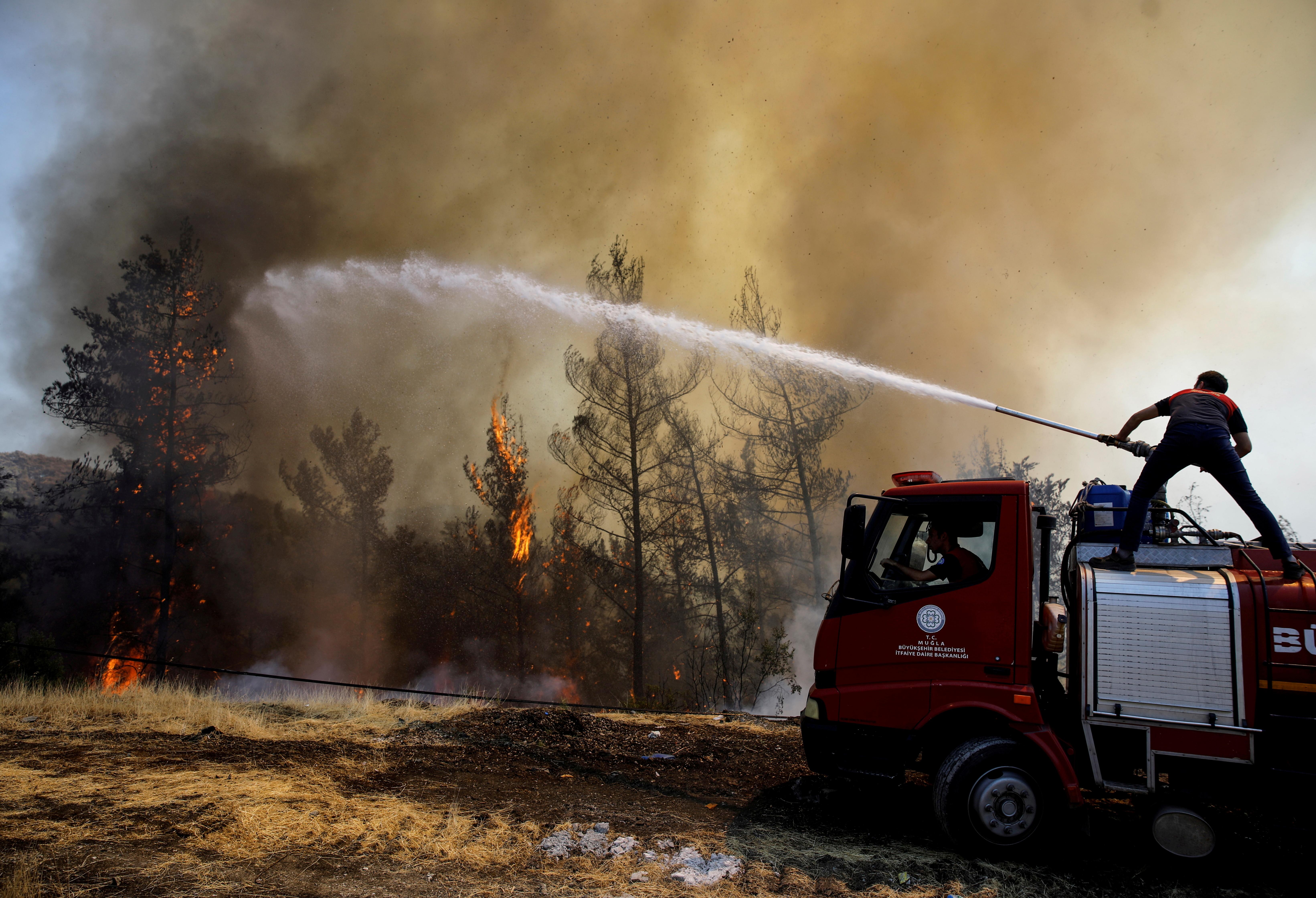 Ugniagesys bando užgesinti gaisrą netoli Marmario, Turkijoje, 1 m. Rugpjūčio 2021 d. REUTERS/Umit Bektas