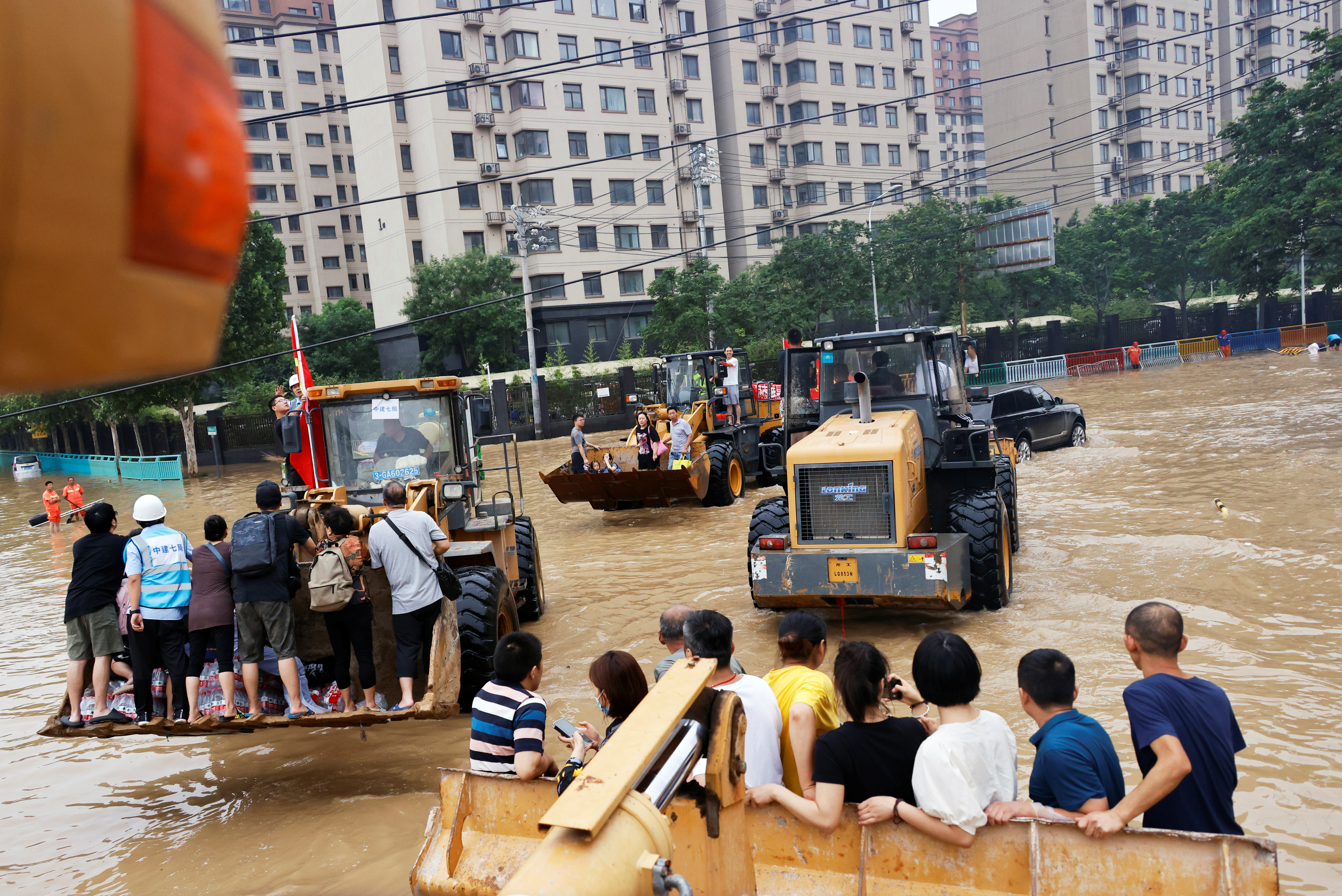 People ride on front loaders as they make their way through a flooded road following heavy rainfall in Zhengzhou, Henan province, China July 23, 2021. REUTERS/Aly Song