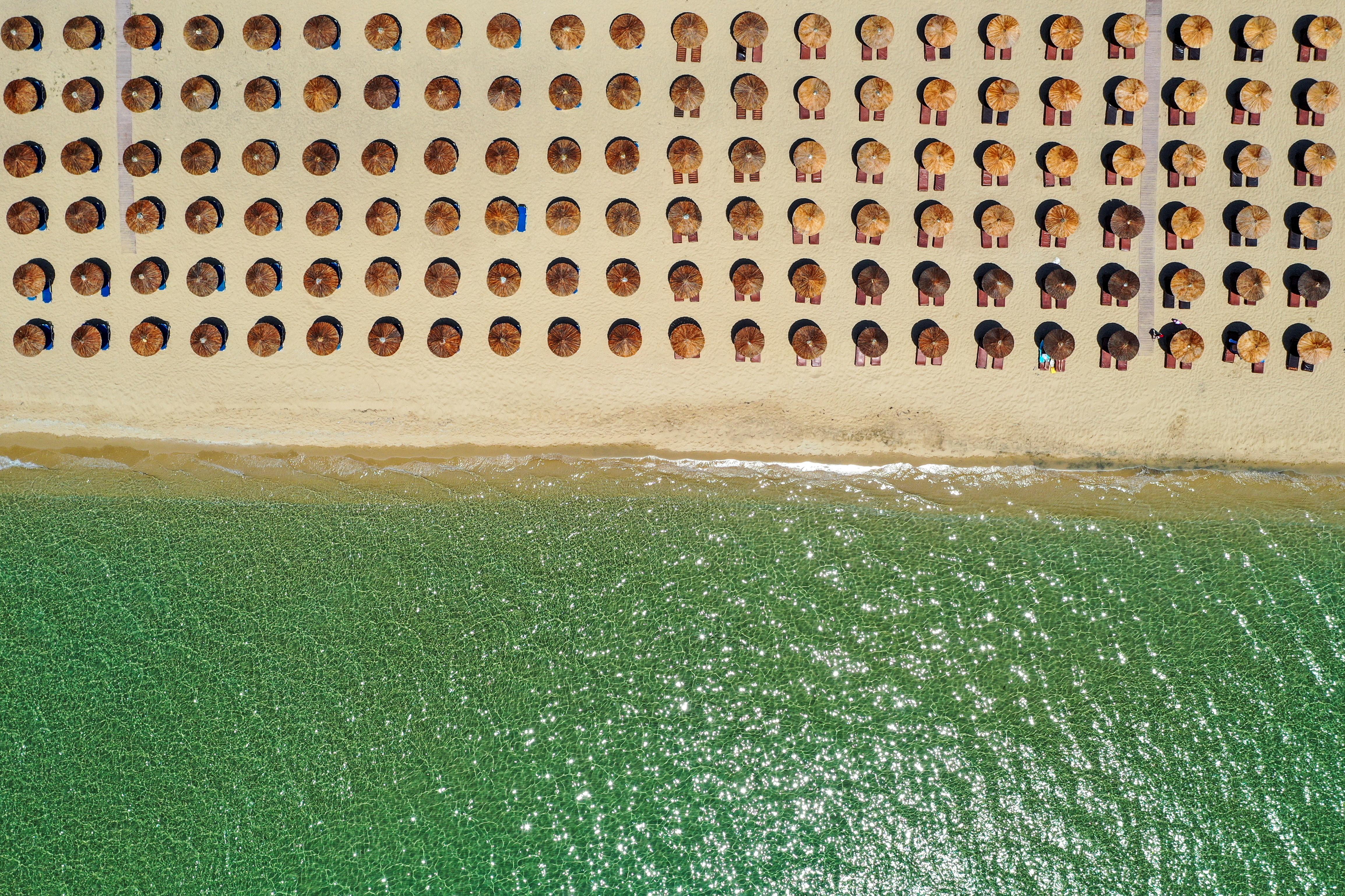 An aerial view shows umbrellas on the Ammolofoi beach in Nea Peramos, Greece June 5, 2021. Picture taken with a drone June 5, 2021. REUTERS/Alexandros Avramidis
