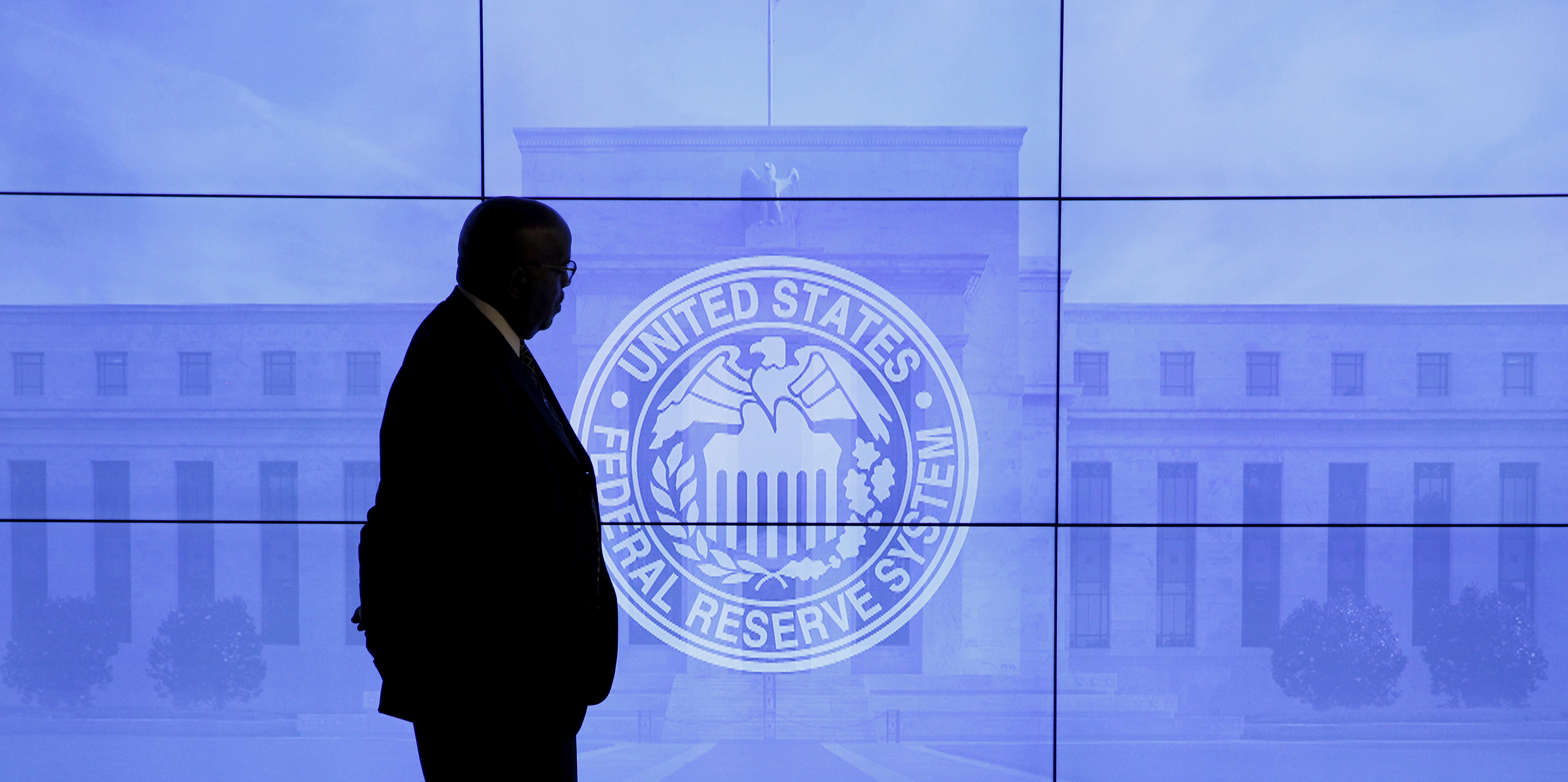 A security guard walks in front of an image of the Federal Reserve following the two-day Federal Open Market Committee (FOMC) policy meeting in Washington, DC, U.S. on March 16, 2016. REUTERS/Kevin Lamarque/Files