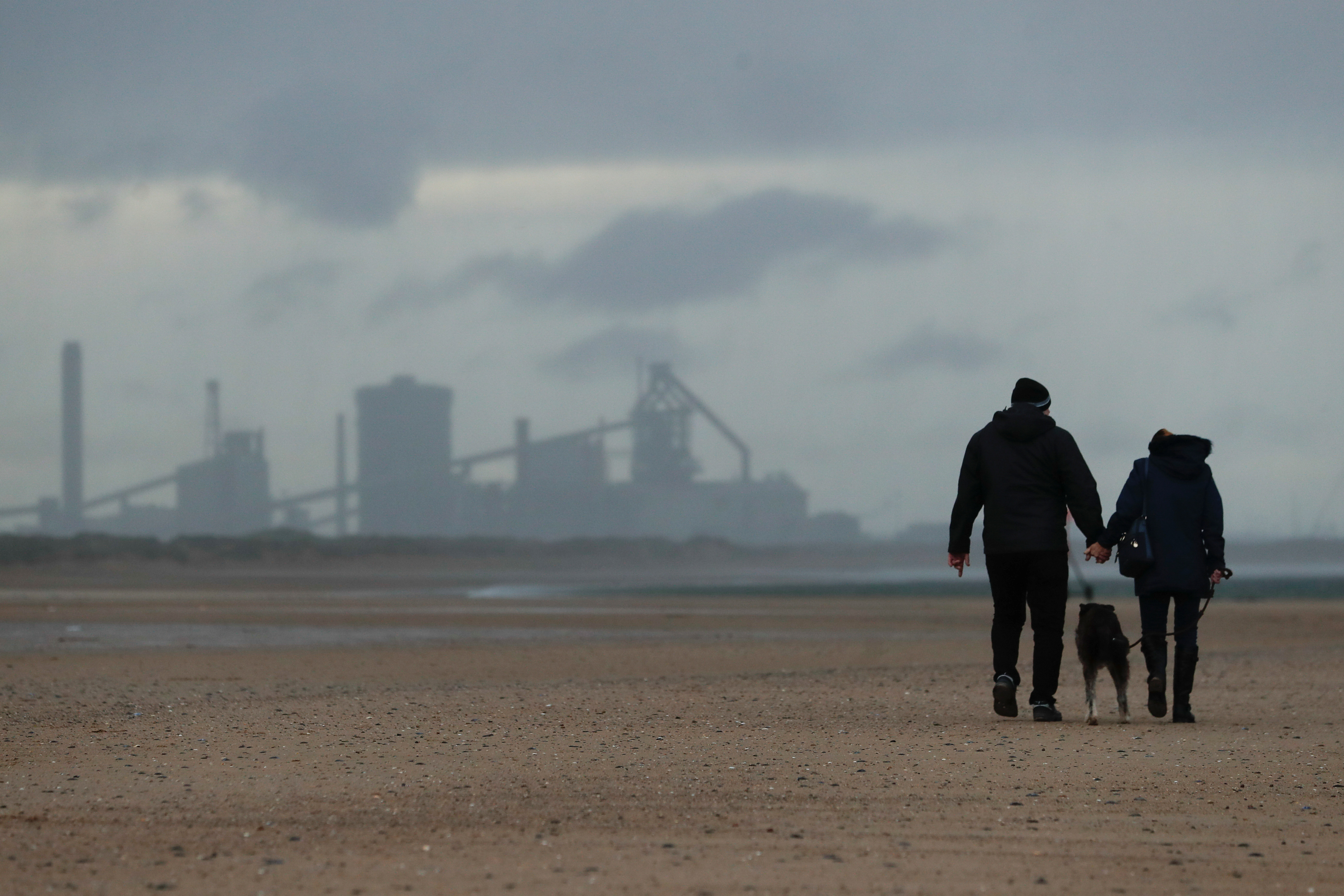 People walk on the beach as industries are seen in the background in Teesside, Britain November 18, 2020. REUTERS/Lee Smith
